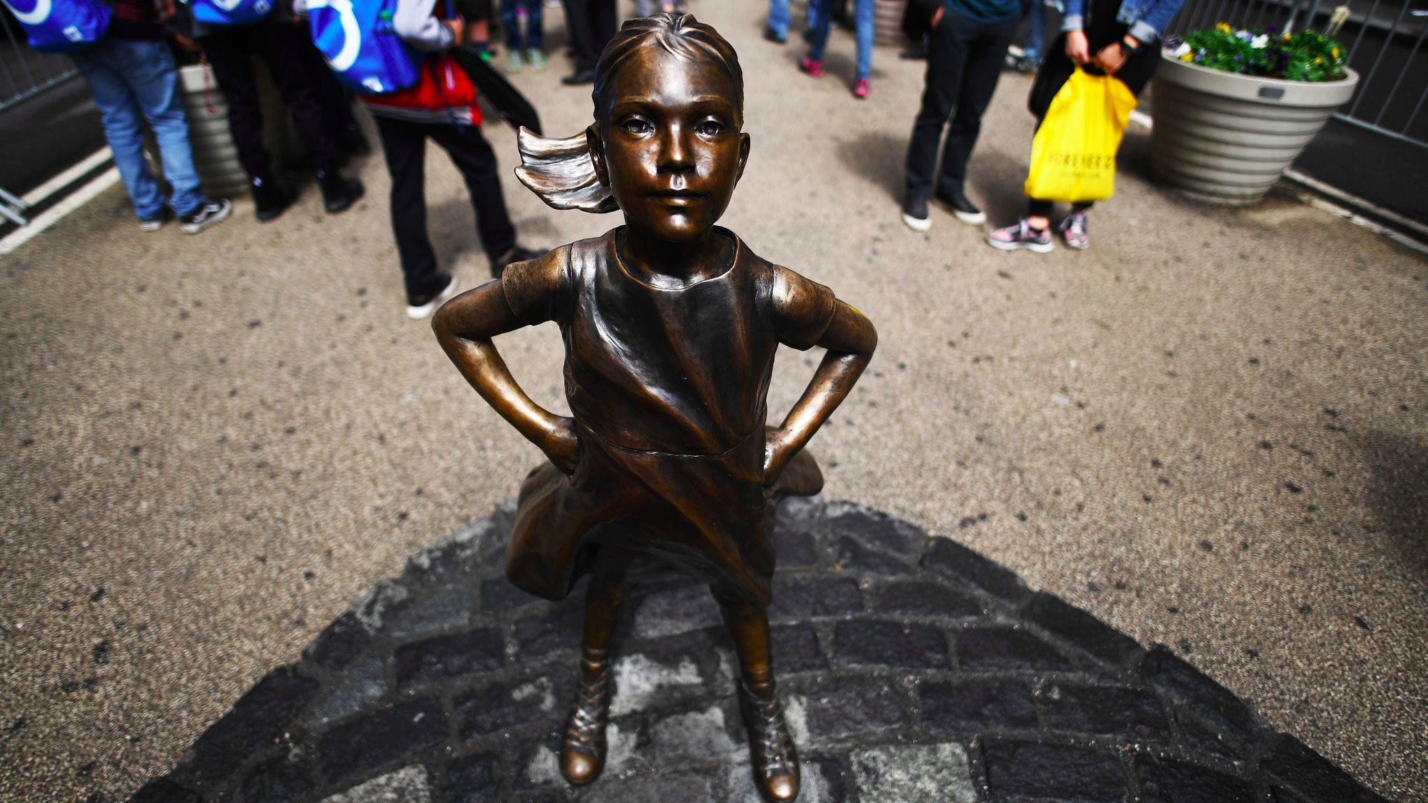 """The """"Fearless Girl"""" statue stands facing the Charging Bull statue as tourists take pictures in New York on April 12."""