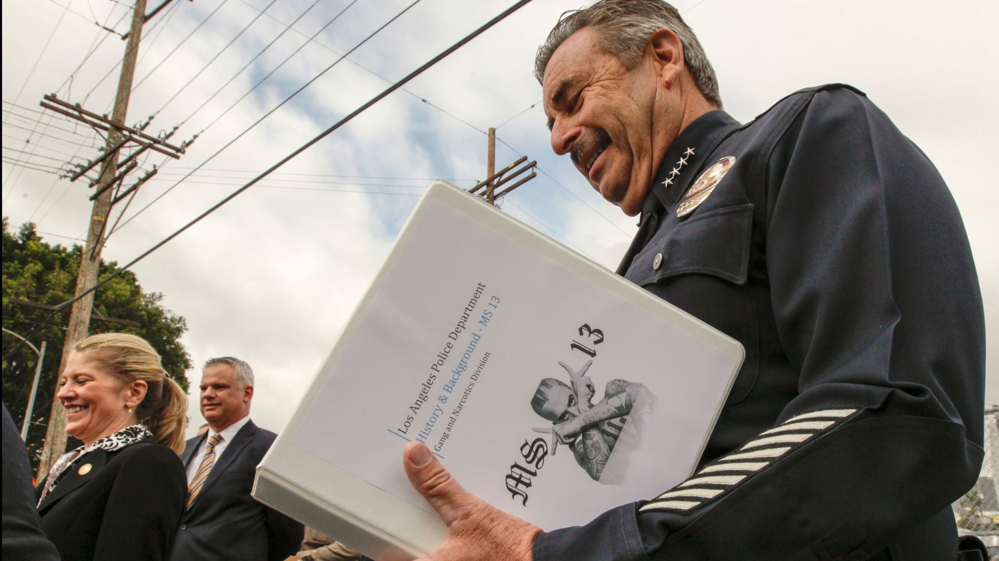 LAPD chief Charlie Beck reads the research on MS-13 gang before addressing a press conference.