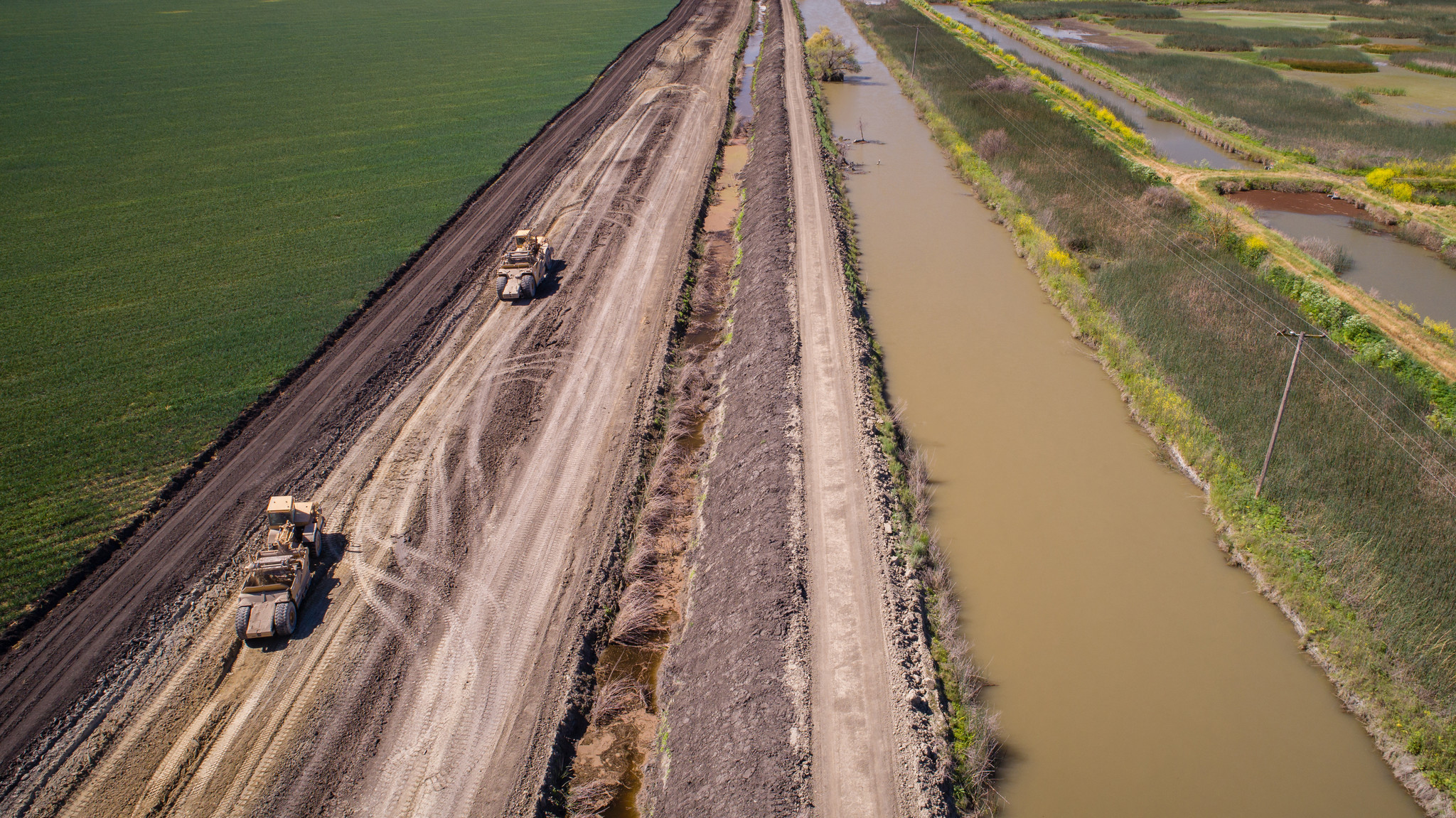 Earth movers carry dirt from a farm field to shore up levees at the Kings River and Fresno Slough in preparation for coming snowmelt.