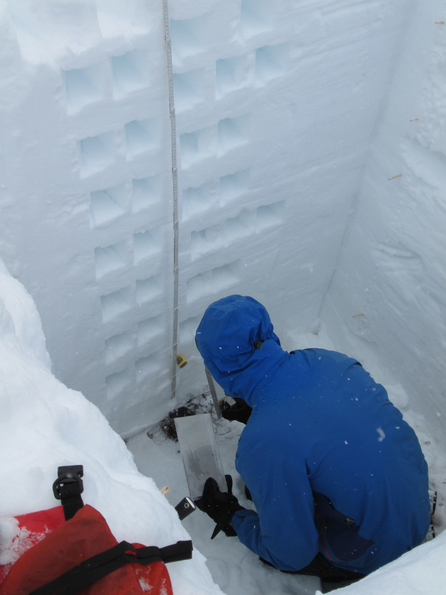 A SnowEx scientist calculates the snow water equivalent by carving out a section of smoothed wall in a snow pit on Feb. 6.