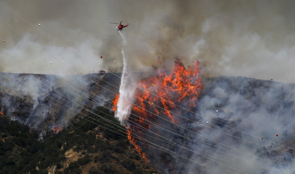 Helicopter drops water on forest fire in Duarte, Calif., on June 20, 2016
