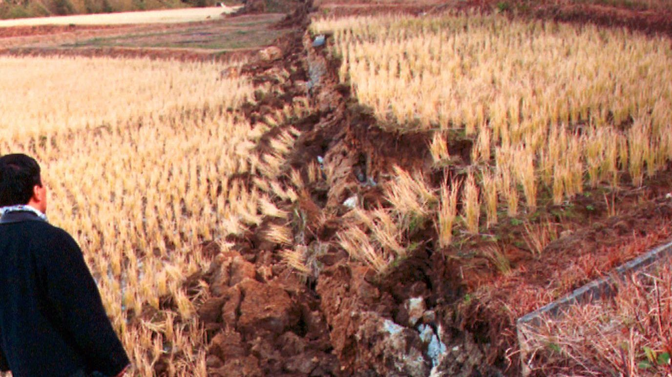 Researchers inspect a fissure running through fields for five miles following an earthquake near Kobe, Japan, in 1995..