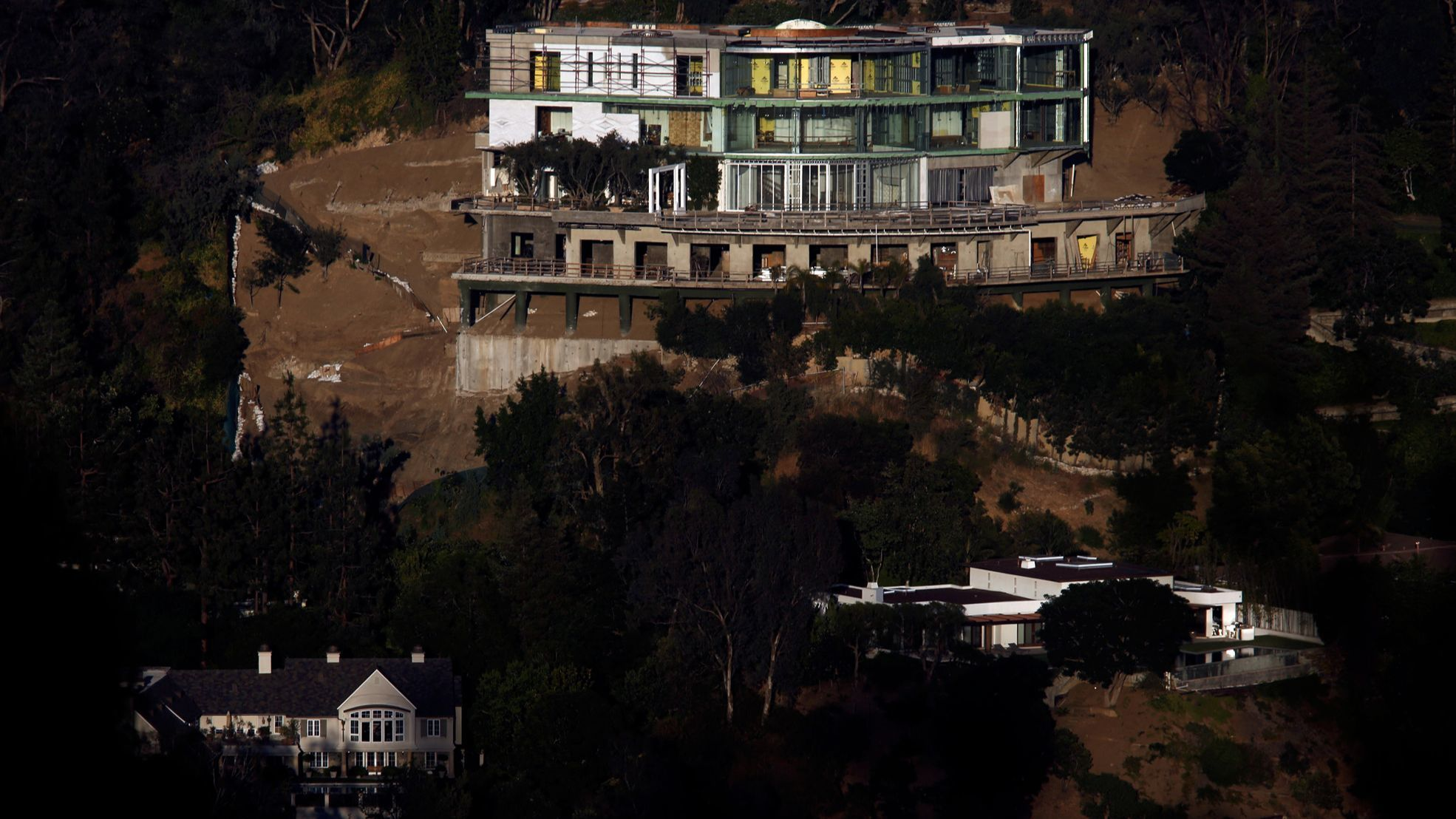 The unfinished mansion towers over a pair of homes in Bel-Air.