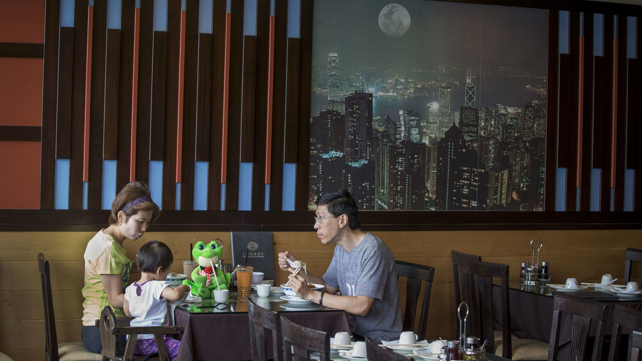 For tasty Cantonese meals, families flock to one of the city's most popular eateries, Sam Woo. In the background, a picture of Hong Kong.