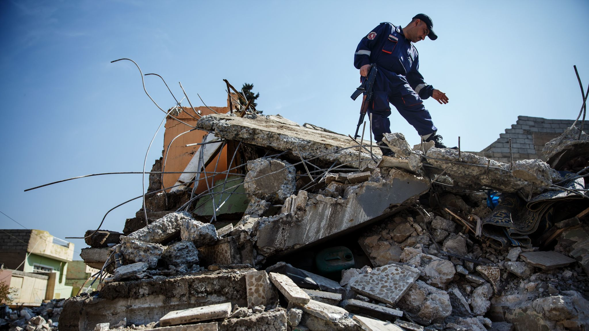 An Iraqi civil defense force member stands guard while work is done to remove the rubble and dead bodies from a home destroyed by a coalition air strike in the  Jadidah neighborhood of Mosul  on March 24, 2017.