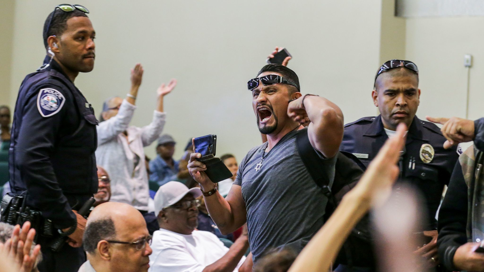 Harim Uzziel, center, a friend of Schaper's and fellow member of the L.A. County for Trump coalition, is escorted from a town hall meeting held by Rep. Maxine Waters in Inglewood in May.
