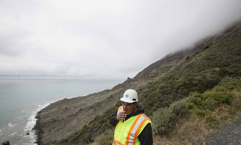 Caltrans resident engineer Rick Silva surveys the area above Highway 1 where a massive landslide obliterated the road.