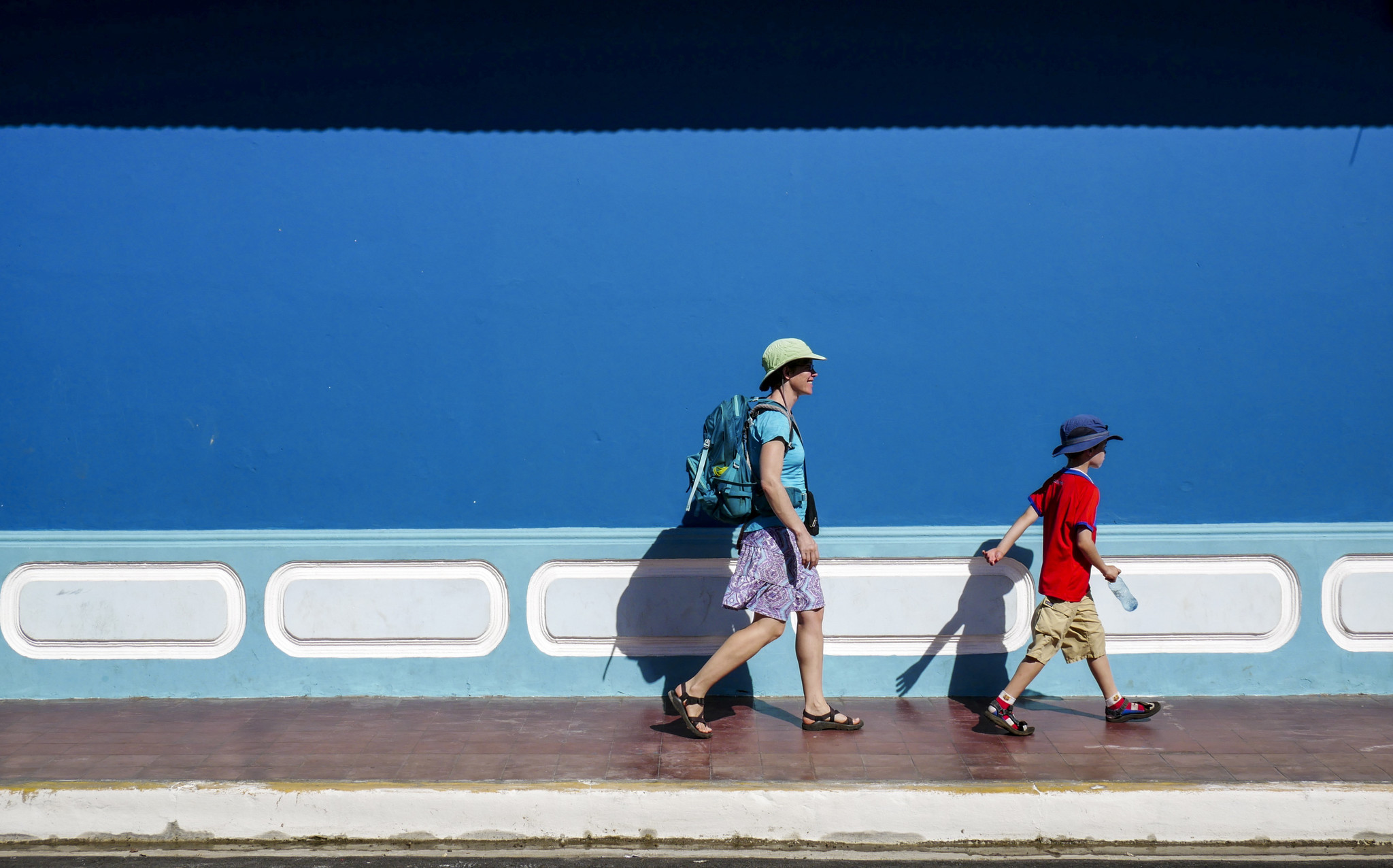 Katie Quirk and son Liam hurry past one of Granada's many bright facades in search of shade.
