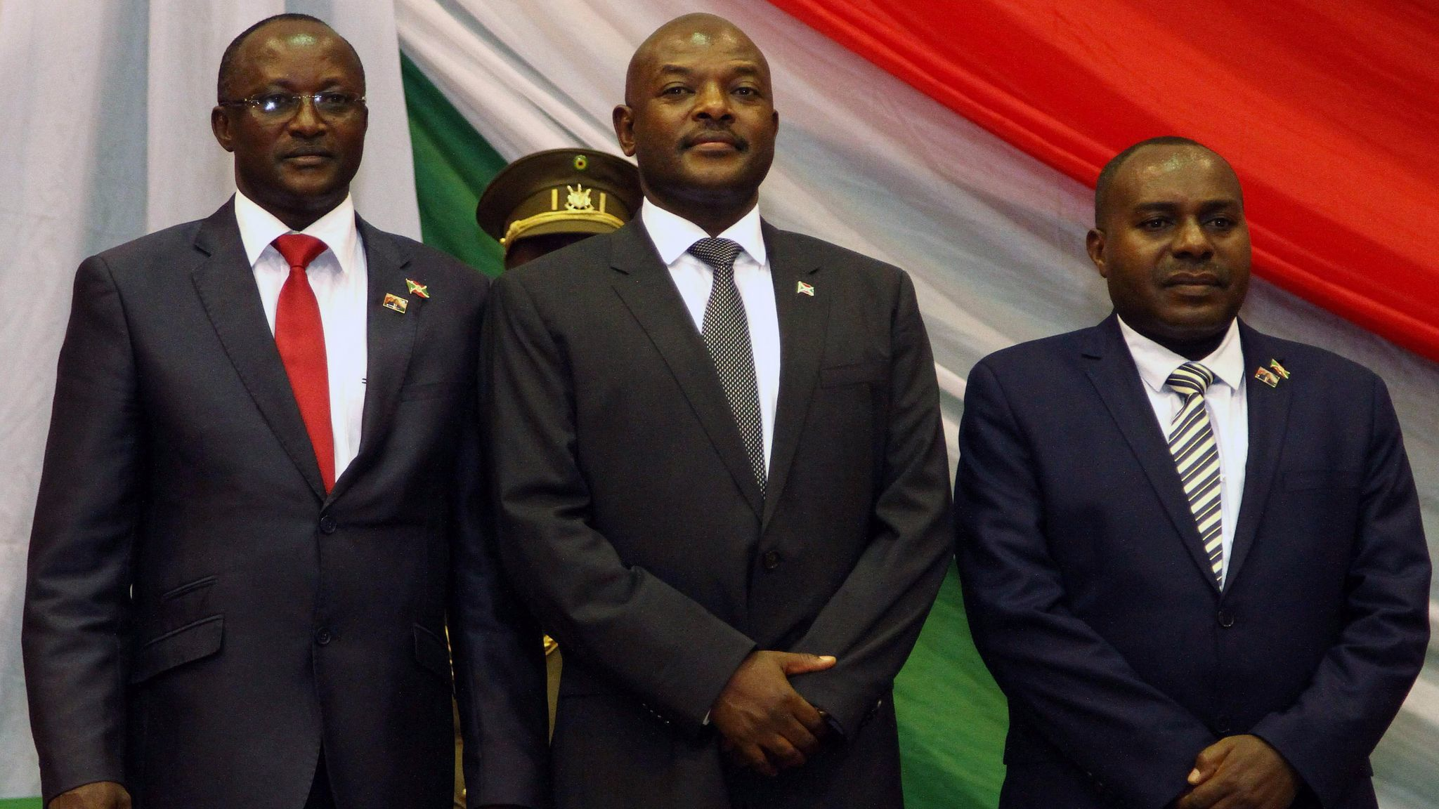 Burundi's President Pierre Nkurunziza, center, with his new first and second vice presidents Gaston Sindimwo and Joseph Mutore, after being sworn in for a controversial third term. In a speech afterward he swore his opponents would be crushed by God.