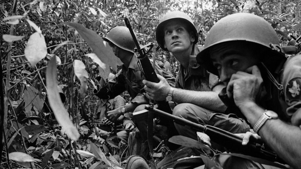 Army Spc. Nelson A. Parker calls for air power support as a U.S. patrol is surrounded by Viet Cong forces in the jungle 20 miles north of Saigon on Feb. 15, 1965.