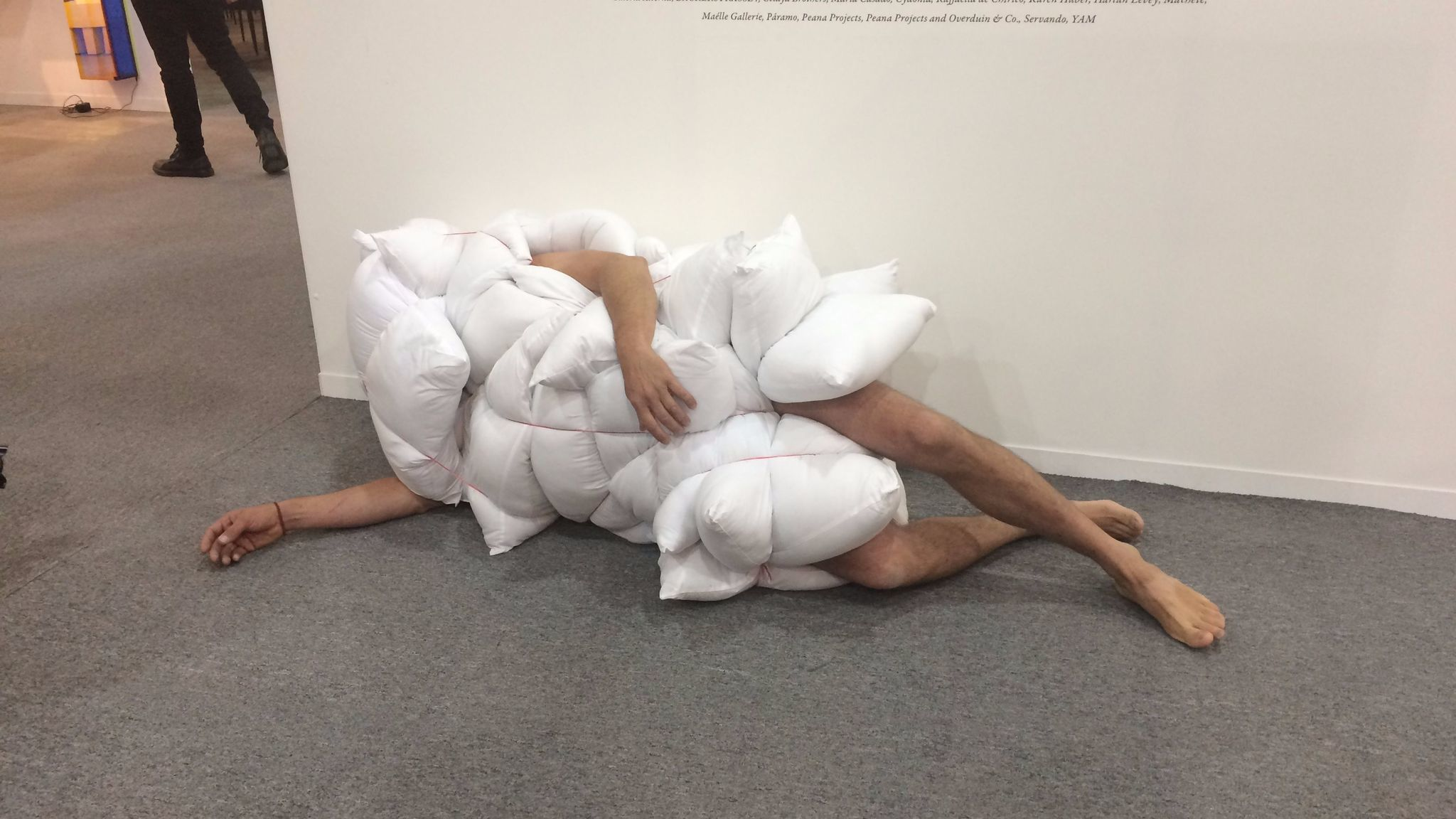 A performance artist covered in pillows at the Zona Maco art fair in Mexico City in February.