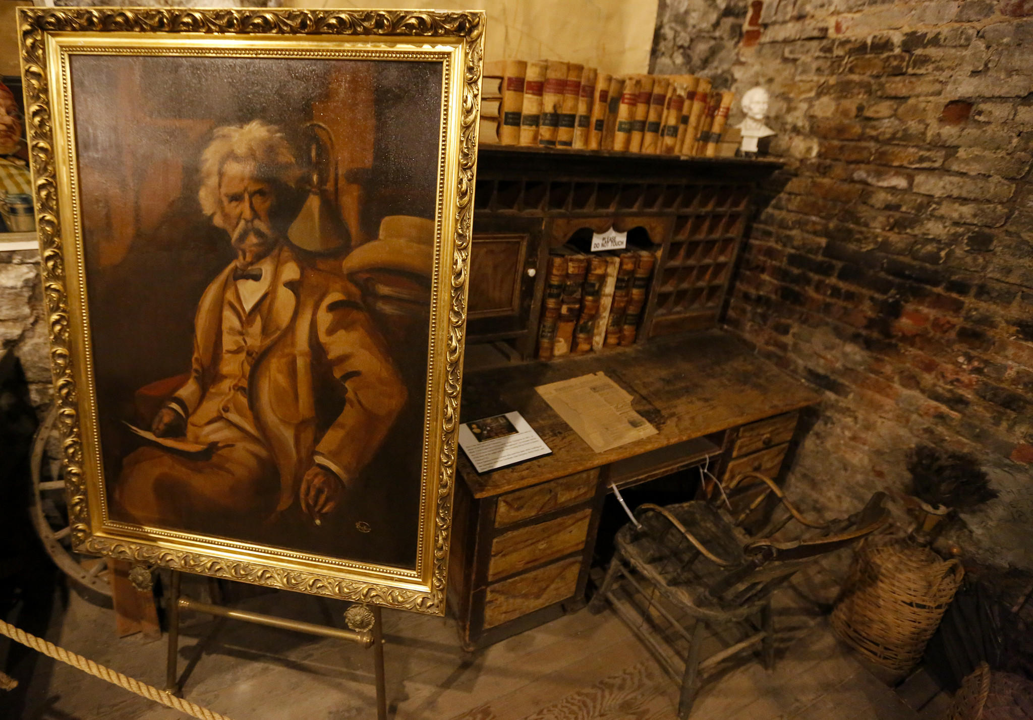 The Mark Twain Museum and Territorial Enterprise Office is in the basement of a store on C street in Virginia City. The desk possibly used by Twain is in the corner of the museum, with a portrait of the author on an easel.