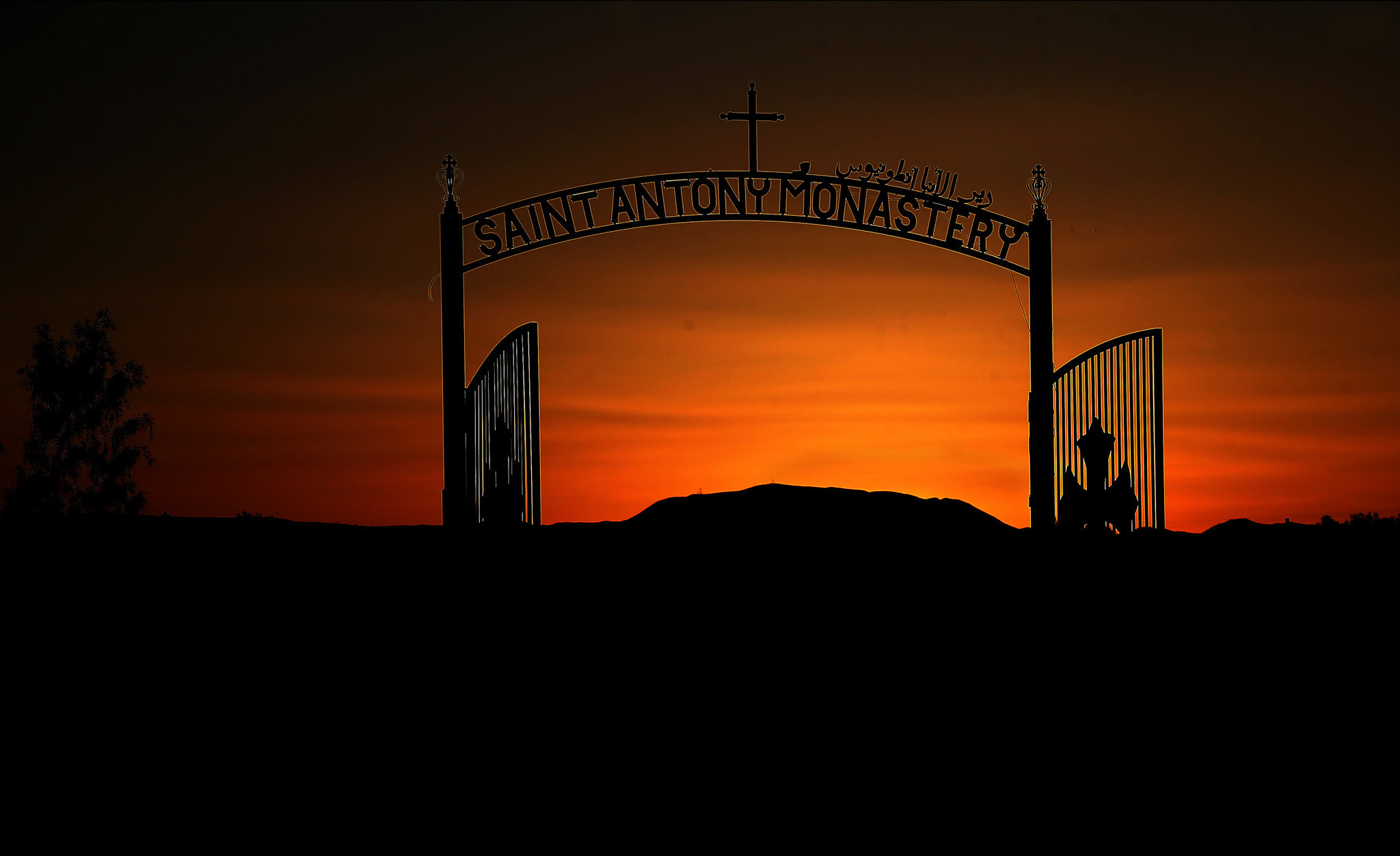 The sun sets behind the entrance to St. Antony Coptic Orthodox Monastery in Newberry Springs.