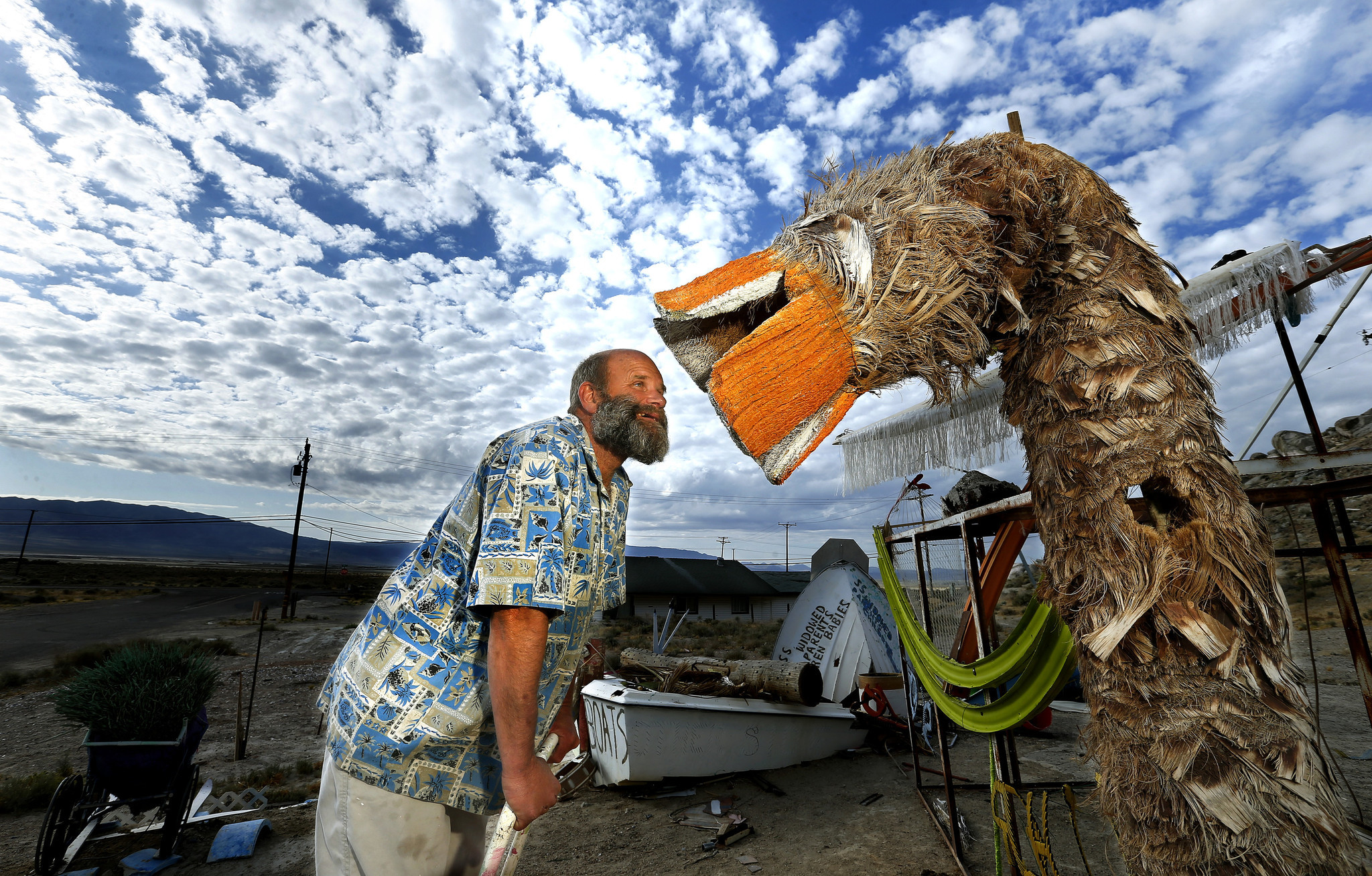 William Fuller III is photographed next to his art installation in front of his home in Trona.