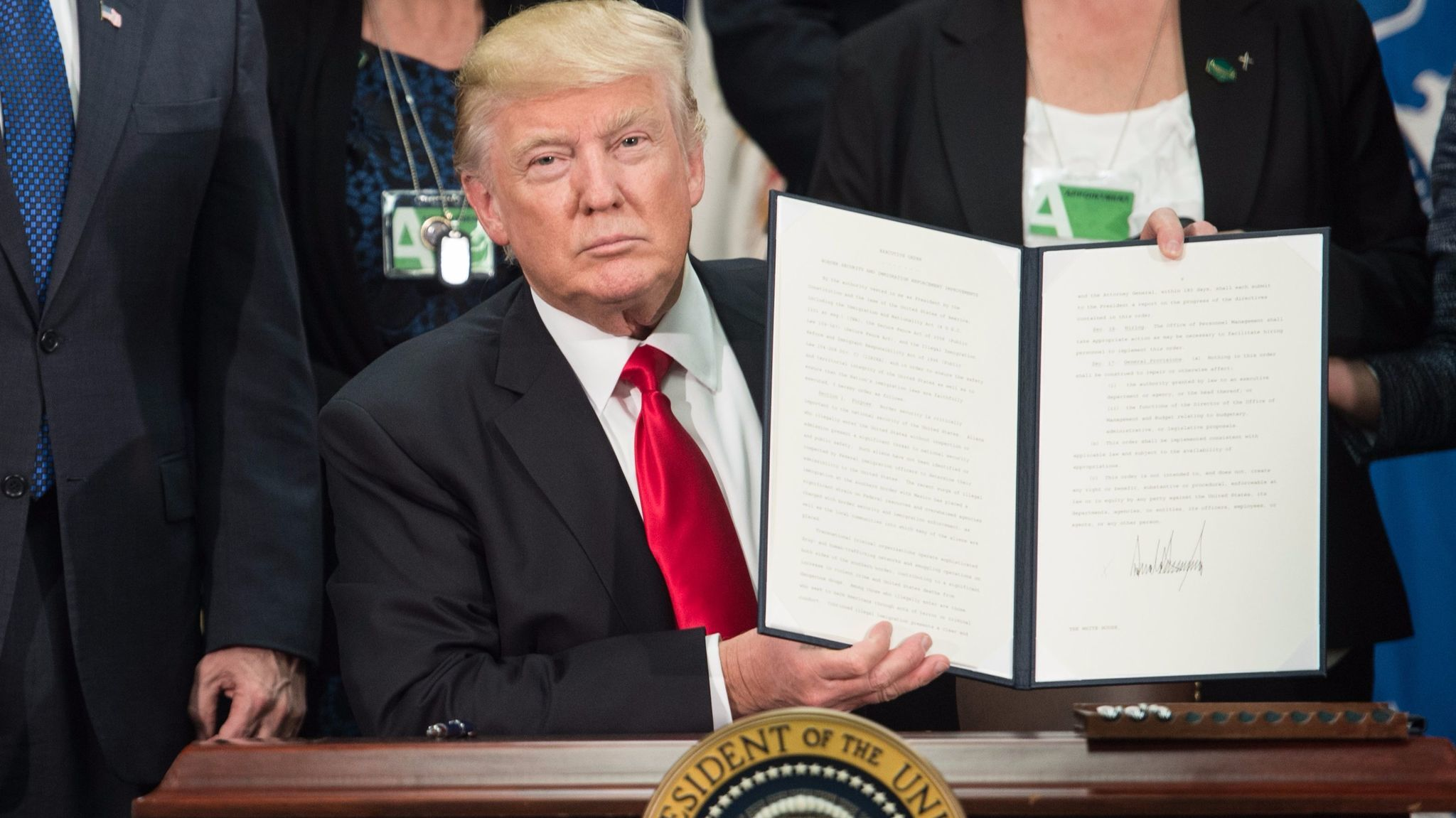 President Trump signs an executive order to start the Mexico border wall project on Jan. 25.