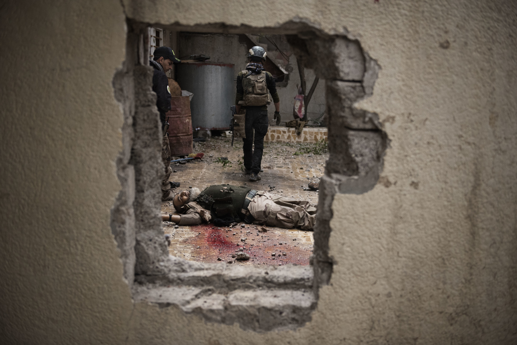 Soldiers walk past an Islamic State fighter killed during a house to house advance in west Mosul, Iraq.