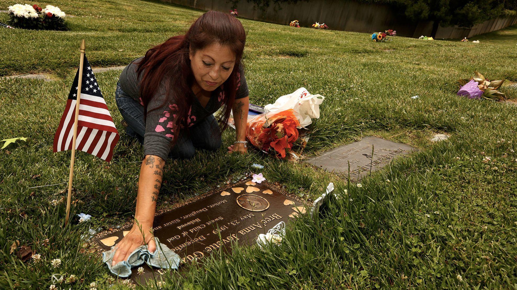 Darlene Guzman cleans her daughter Bree'Anna Jovette Guzman's gravesite at Forest Lawn Memorial Park in Glendale.
