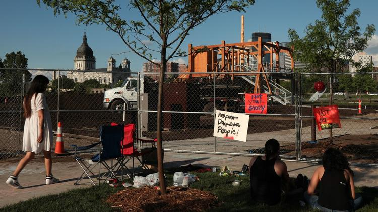Protesters stand outside the Minneapolis Sculpture Garden, the site of Sam Durant's
