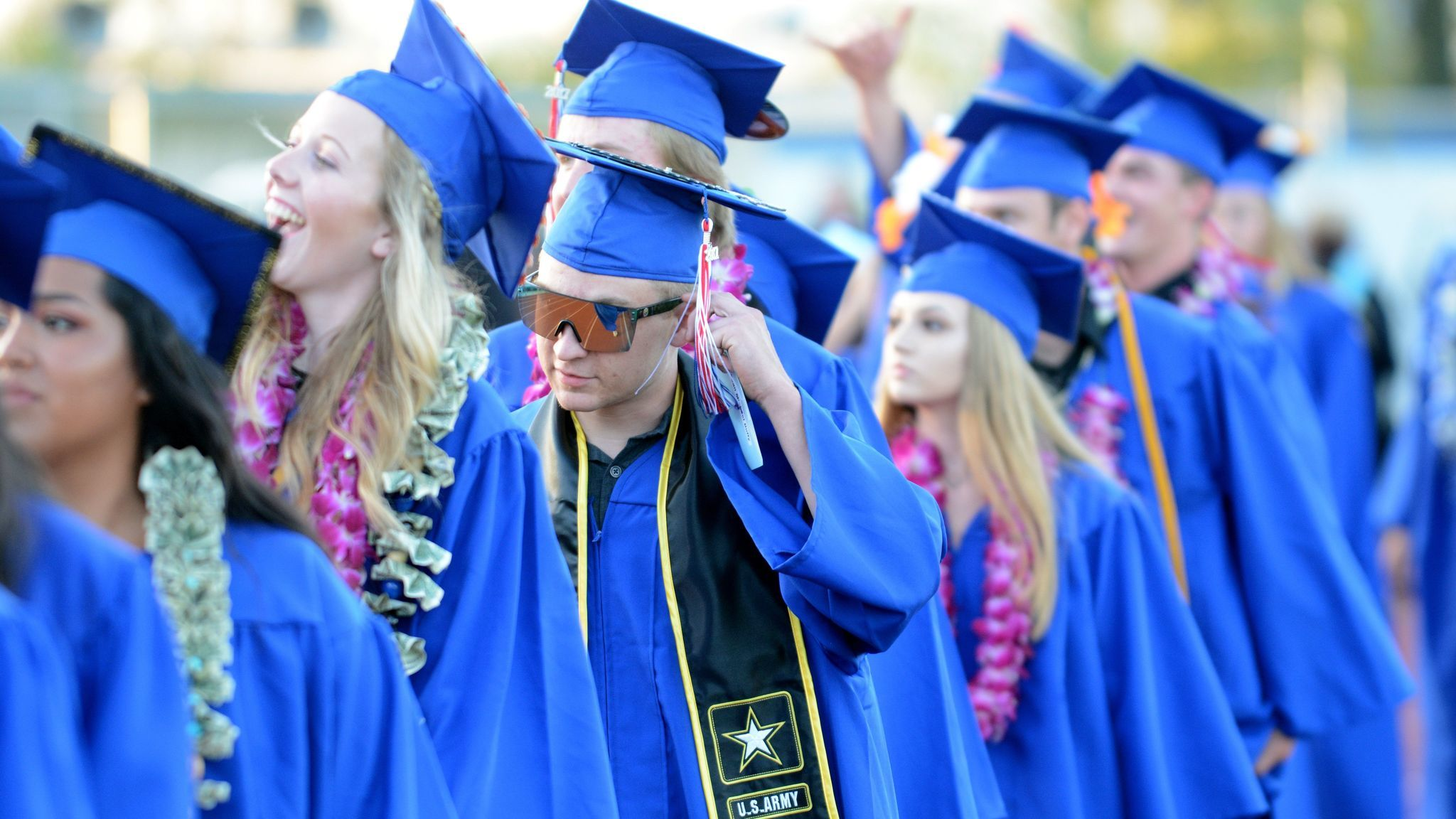 Sean Duffy adjusts his tassel as classmates check the stands for familiar faces when they enter the stadium.