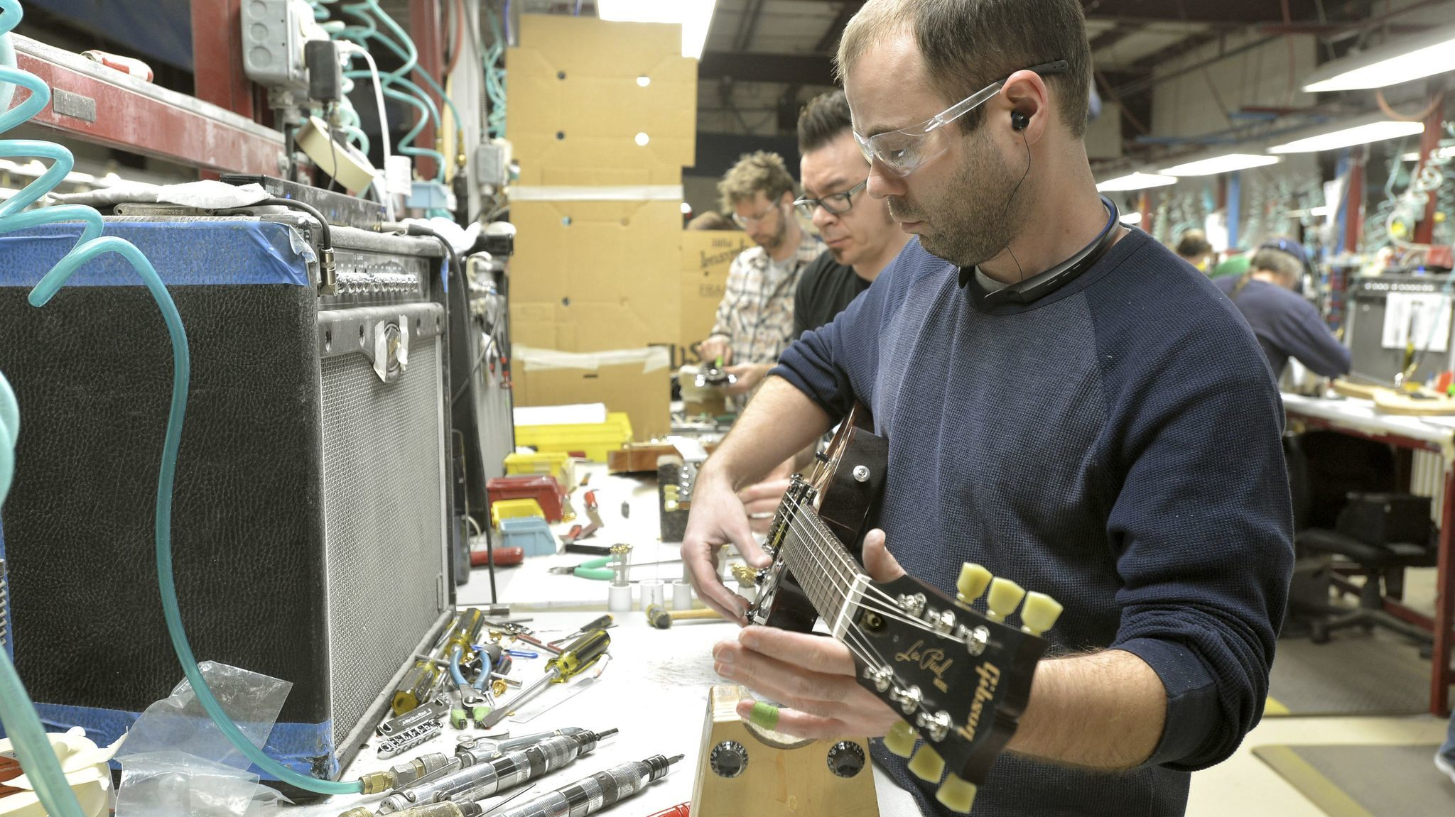 Loren Amsbary makes final adjustments on new guitar at the Gibson guitar manufacturing plant.