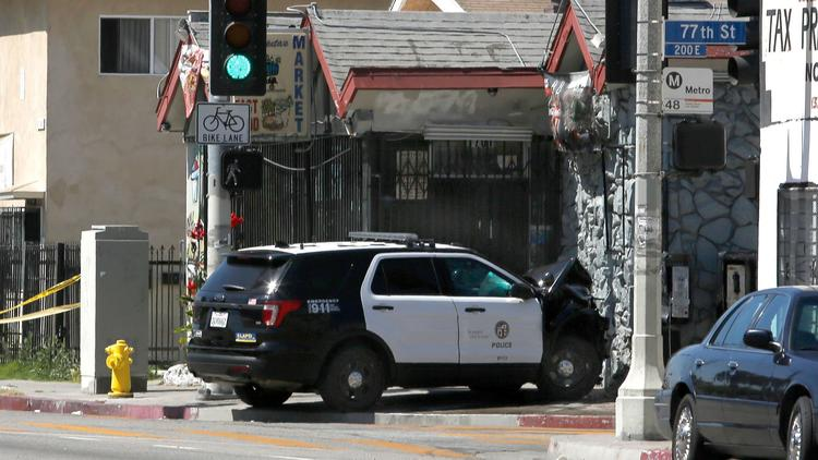 A police SUV rests Thursday where it crashed near the intersection of 77th and San Pedro streets in