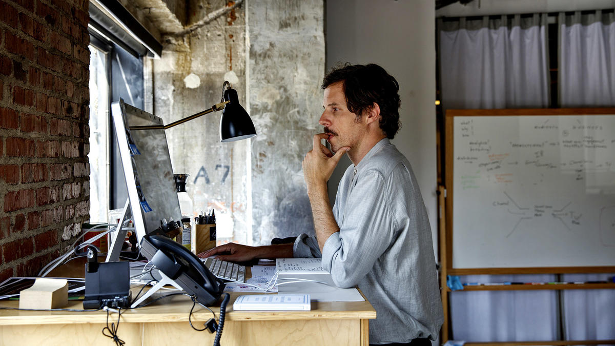 """Wolfgang Hammer, president of Super Deluxe, works at his standing desk in his downtown office. """"We're telling the audience: You can choose your own adventure,"""" he said."""