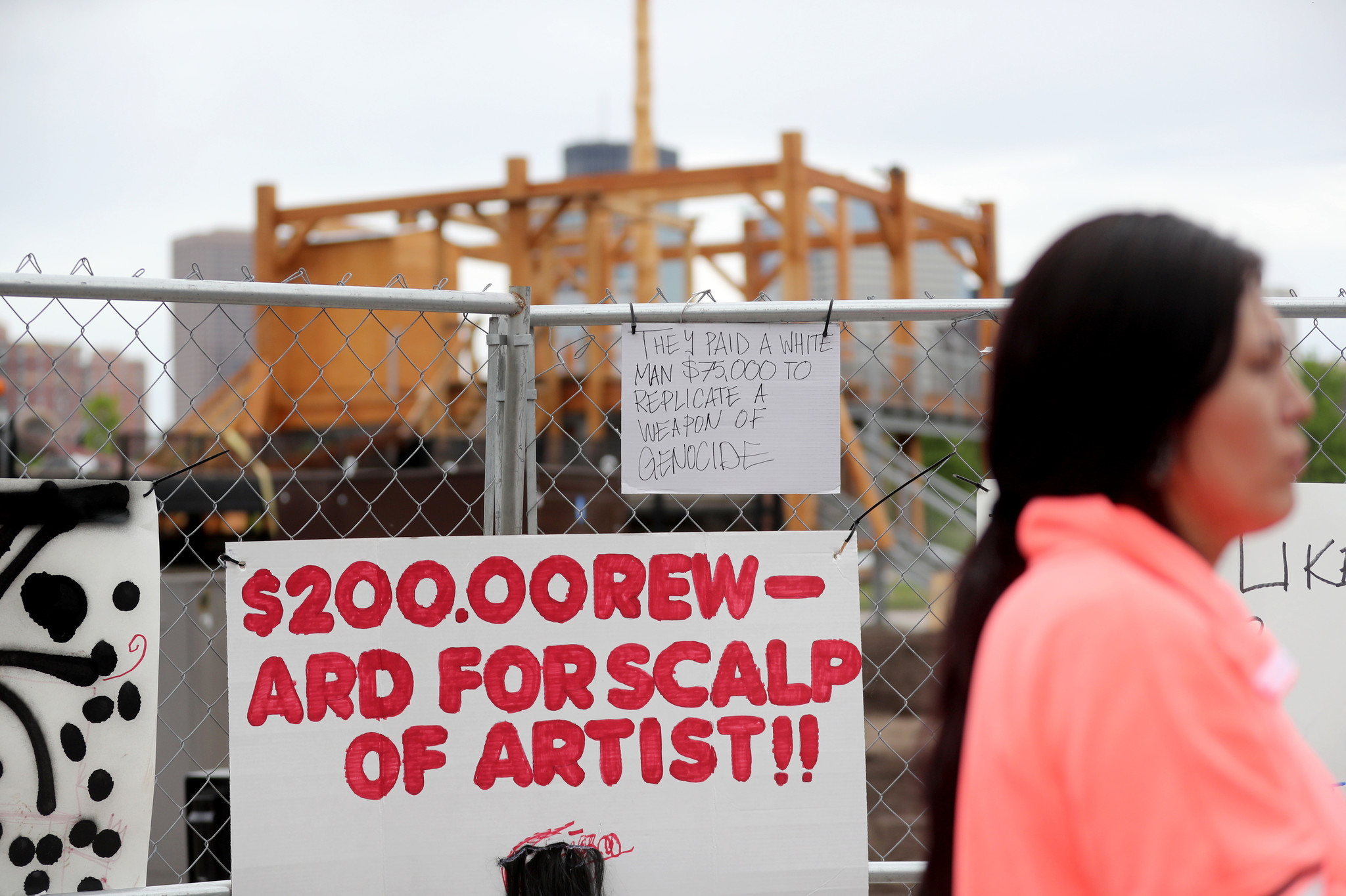 Protest signs outside the Walker Art Center's Minneapolis Sculpture Garden before artist Sam Durant's sculpture