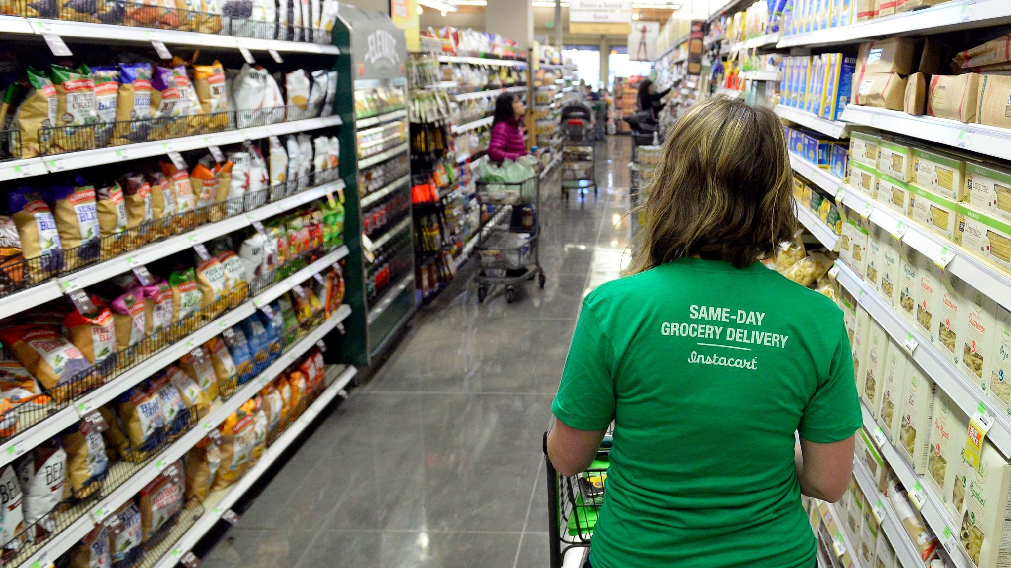 An Instacart shopper looks for groceries at a Whole Foods store in Denver.