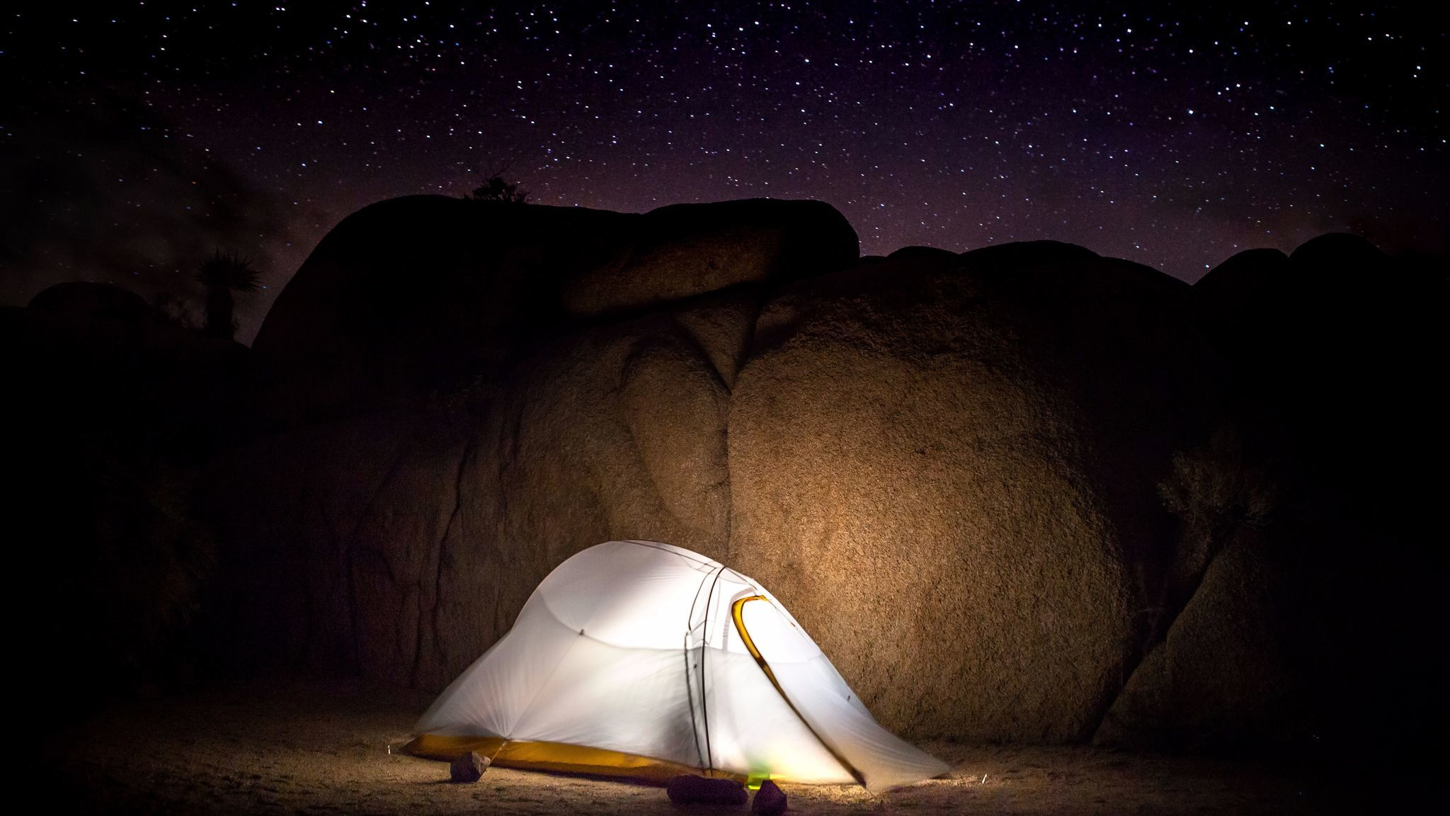 The glow of a tent camp light casts on the large boulders shielding the heavy winds on a starry night at the Jumbo Rocks Campground in Joshua Tree National Park.