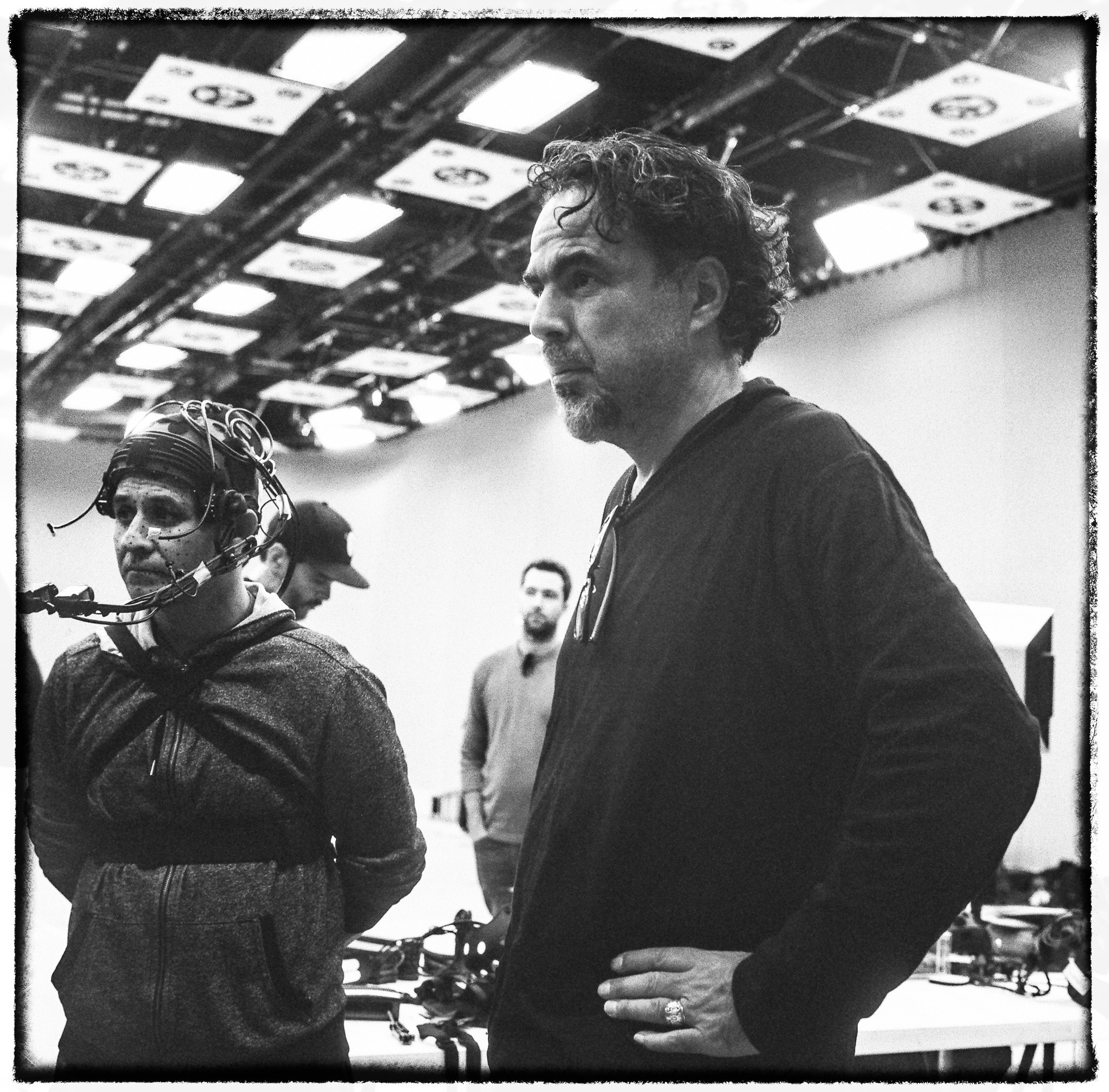 "Alejandro G. Iñárritu, right, on the set of ""Carne y Arena"" with a baker from El Salvador named Yoni, who is dressed in a motion-capture suit to help re-create a harrowing moment on his journey to the U.S."