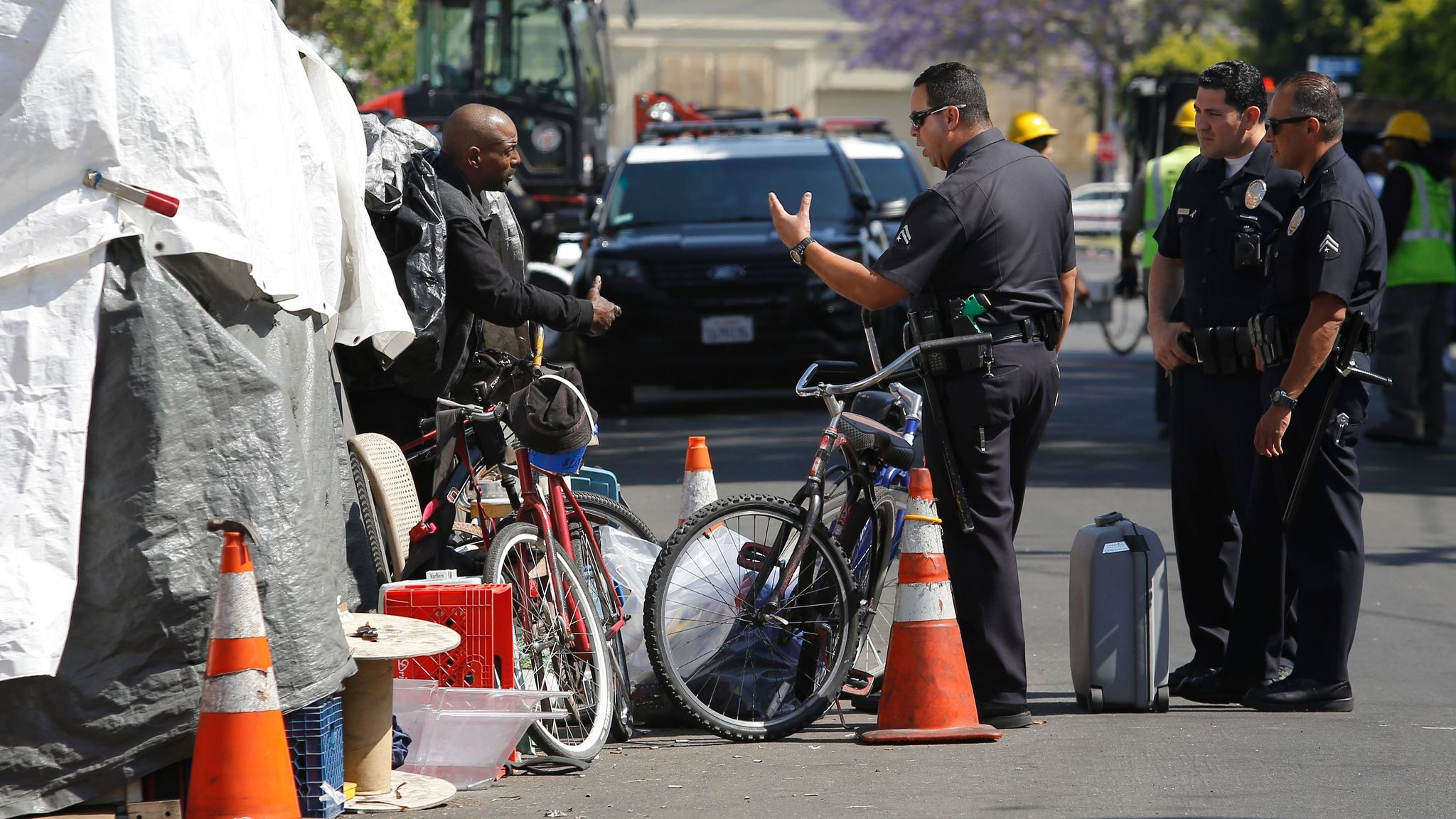 LAPD officers speaks with a man who is living in an encampment area in Los Angeles. Sanitation workers later cleaned the area.