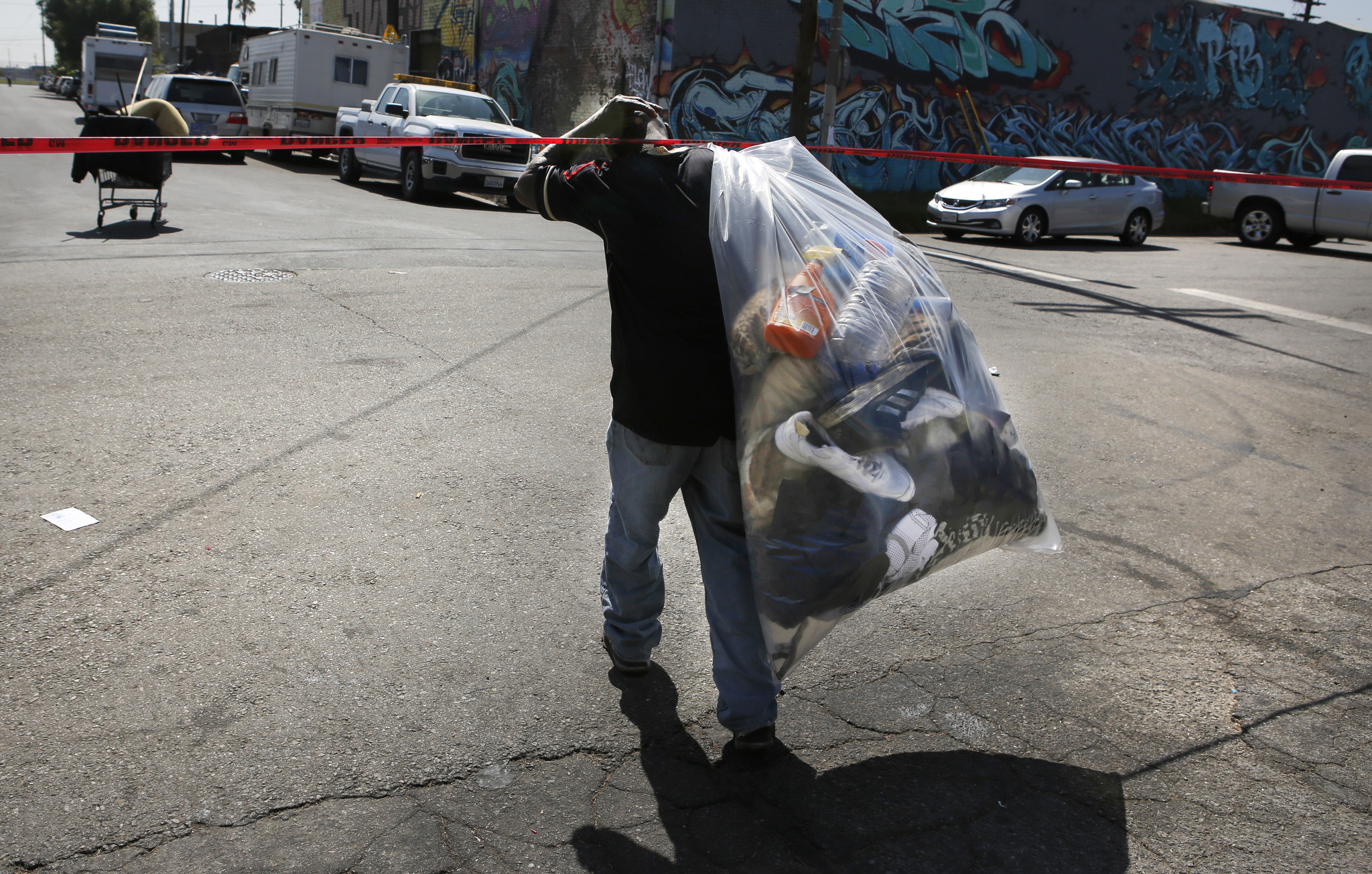 A homeless man leaves an encampment area with his belongings in a bag.