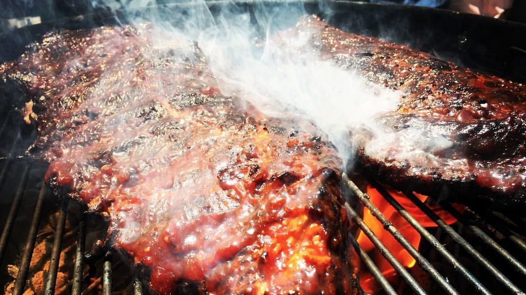 Finishing a rack of ribs with a light brushing of barbecue sauce just before taking off heat.