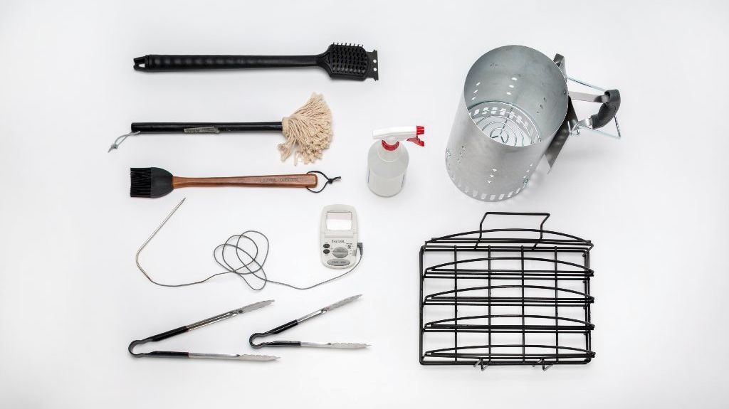 Essential rib tools, clockwise from center: spray bottle, charcoal chimney, rib rack, tongs (2), digital thermometer, silicone brush, mop, grill brush.