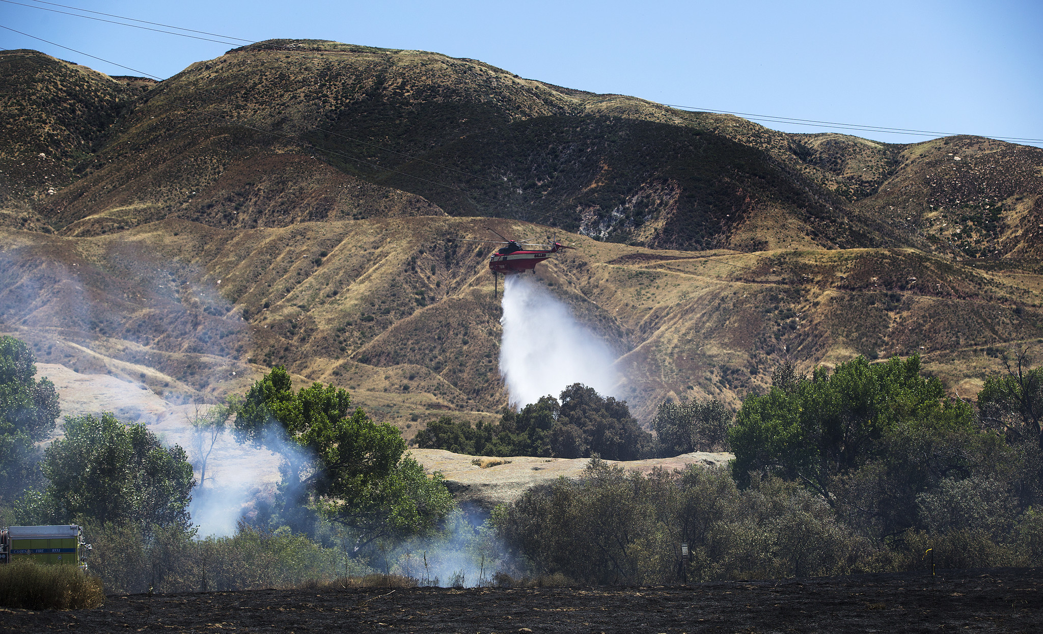 A helicopter drops its water load to stop the advance of the Manzanita fire, which has burned some 6,300 acres of rugged terrain and knocked down power poles off Highland Springs Avenue south of  Beaumont.