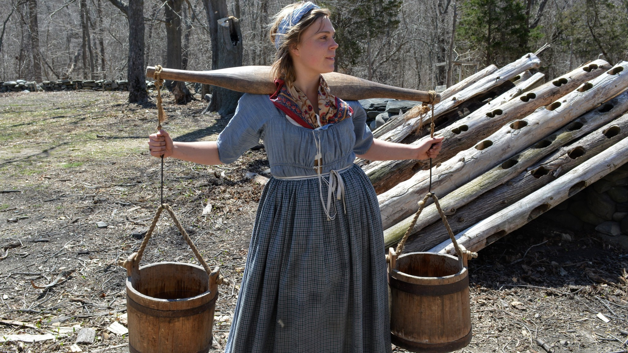 Docent at Coggeshall Farm Museum demonstrates how a yoke would be shouldered to ease the burden of carrying heavy wooden buckets.