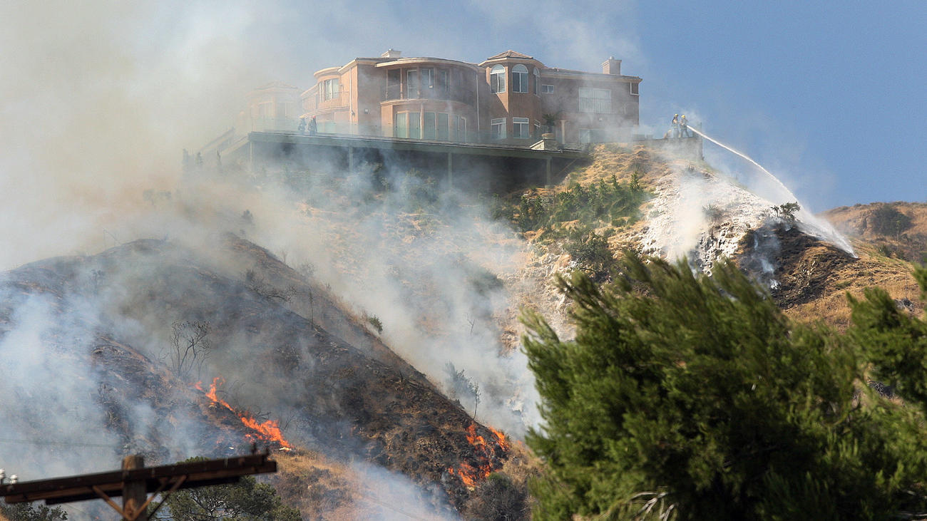 A home on the top of the hill on Irving Drive is protected from a brush fire with a foam sprayed onto the hillside below it in the foothills above Hamline Place in Burbank.