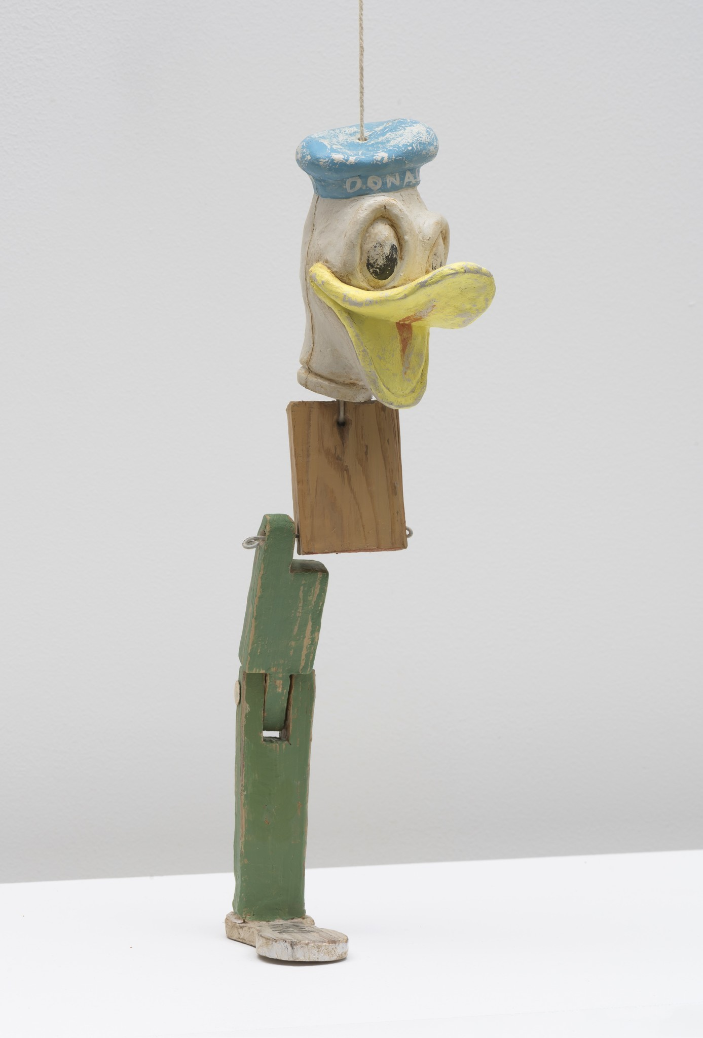 """Kristen Morgin, """"One Legged Donald,"""" 2017, unfired clay, paint, ink. 12.5 inches by 2.5 inches."""