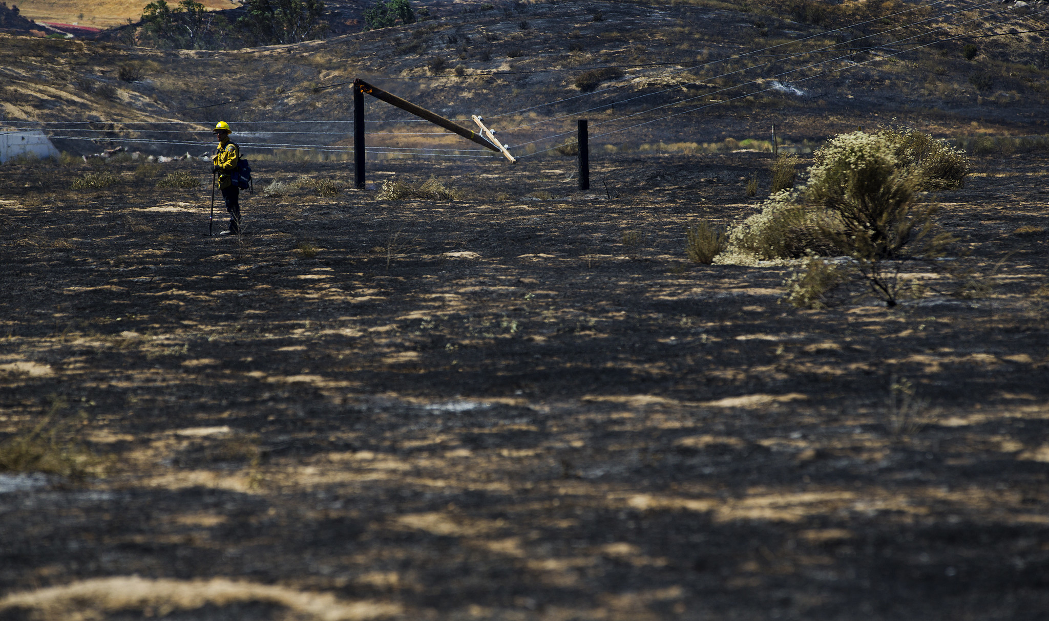 A firefighter checks on hot spots after the Manzanita fire burned 5,800 acres of rugged terrain and knocked down power poles off Highland Springs Avenue on June 27, 2017 south of  Beaumont.