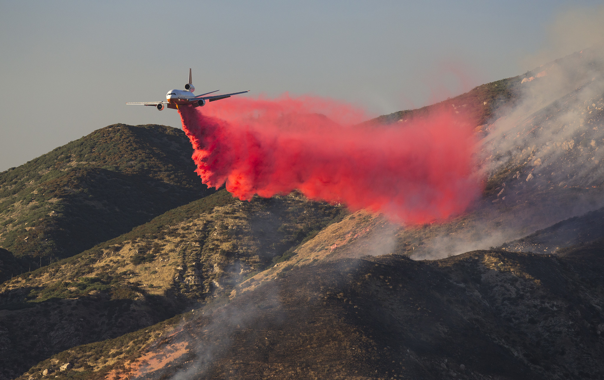 A plane drops fire retardant on the hillsides to battle the Mart fire  near Highway 330 on June 27, 2017 in Highland, California.