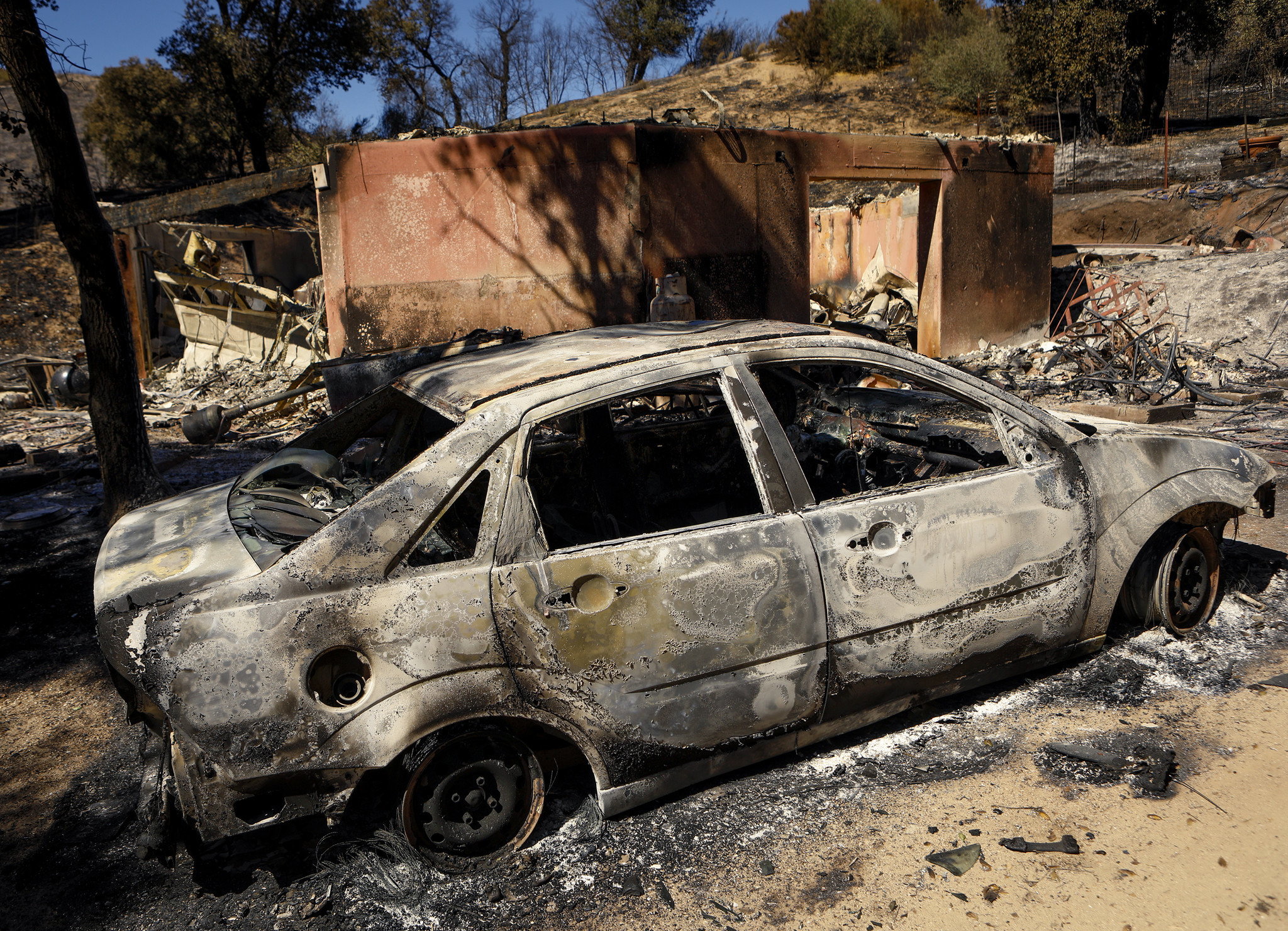 A burned-out car sits next to a destroyed home after a wildfire in Santa Margarita on Wednesday, June 28, 2017.