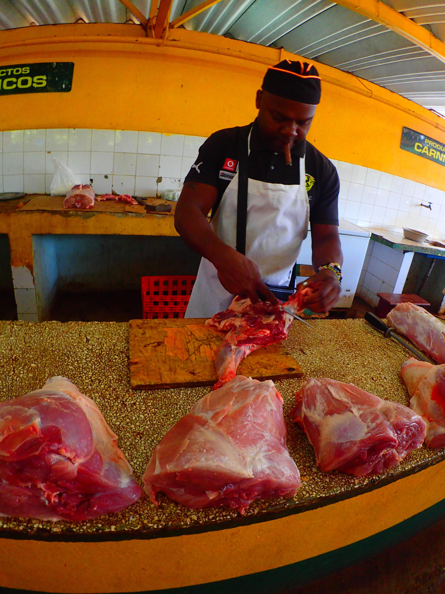 A cigar-smoking butcher hacks away at the day's meat inside a farmers market in Havana's Vedada district.