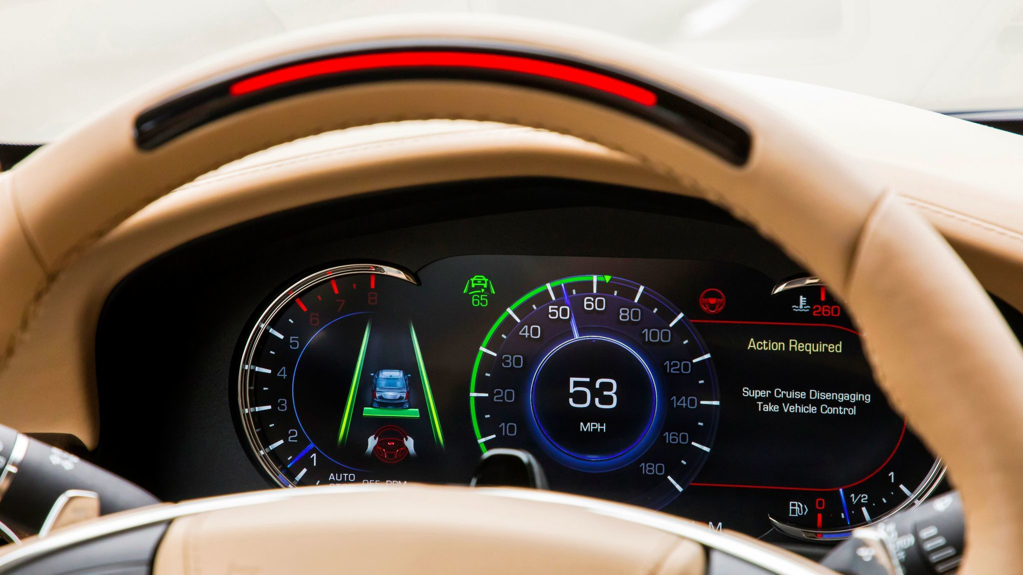 The light bar turns red when the driver needs to turn attention back to the road. If there's no response, a chime sends an audio warning and the red light flashes. A voice alert follows, and soon the car will ease to a stop. The camera can be seen in front of the speedometer.