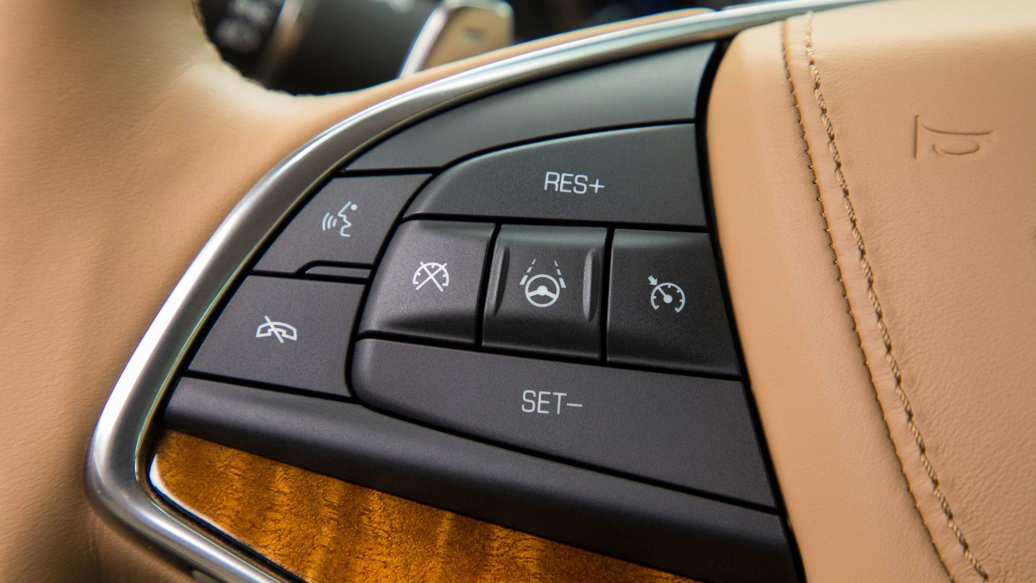 The Super Cruise on/off button on the left side of the steering wheel, center.