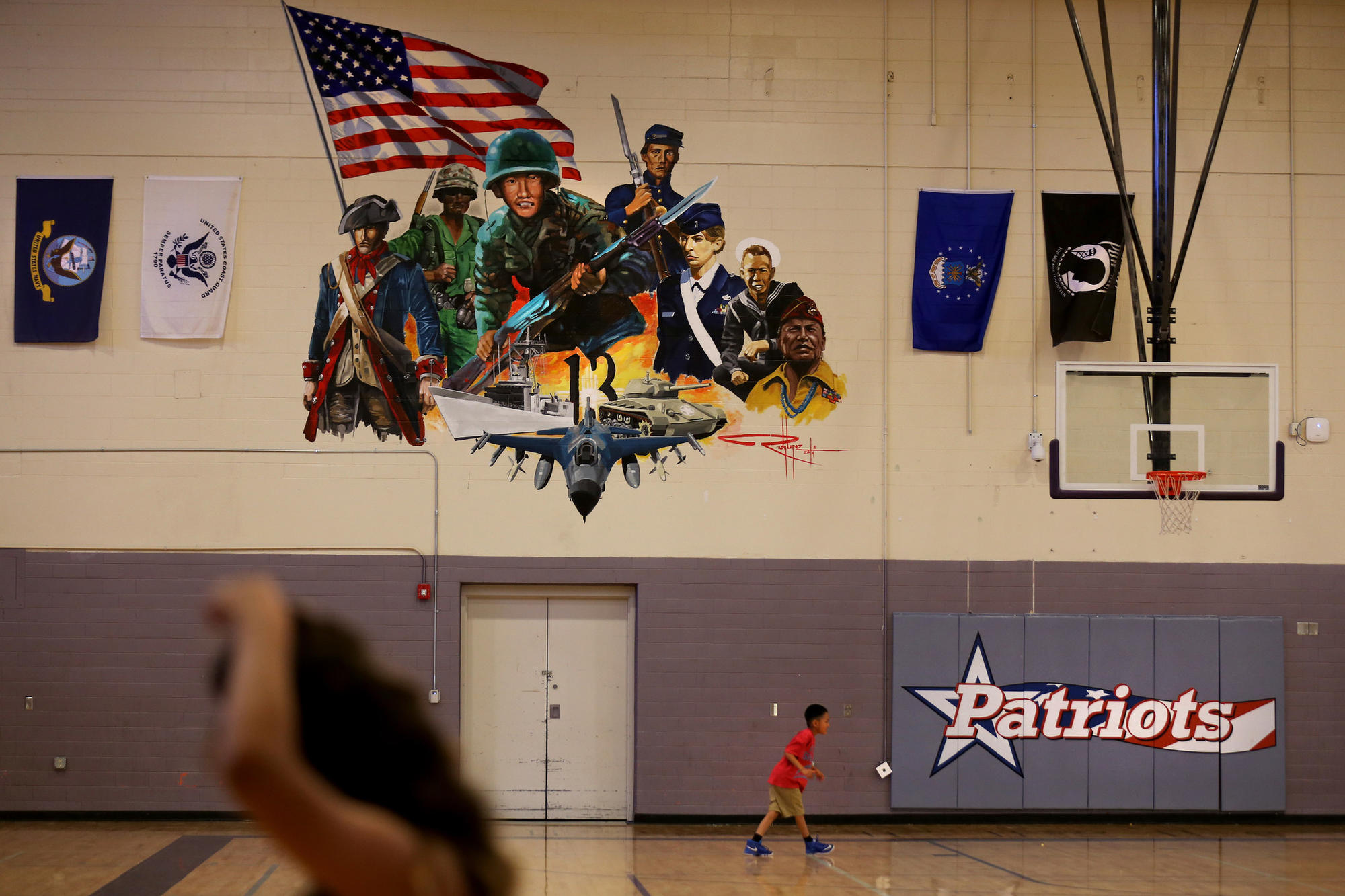 The city of Gallup honored the war hero by naming a school, Hiroshi Miyamura High School, after him. A mural in the gymnasium bears his image, center.