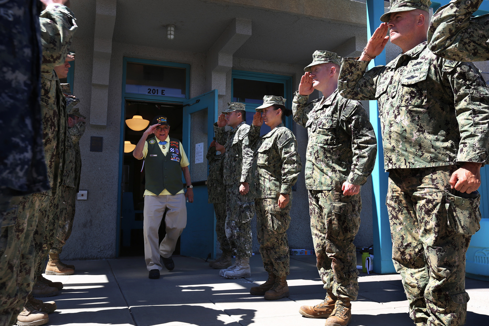 Hiroshi Miyamura is saluted by a group of Navy Seabees after he spoke to them about his war experiences at the Gallup Cultural Center.