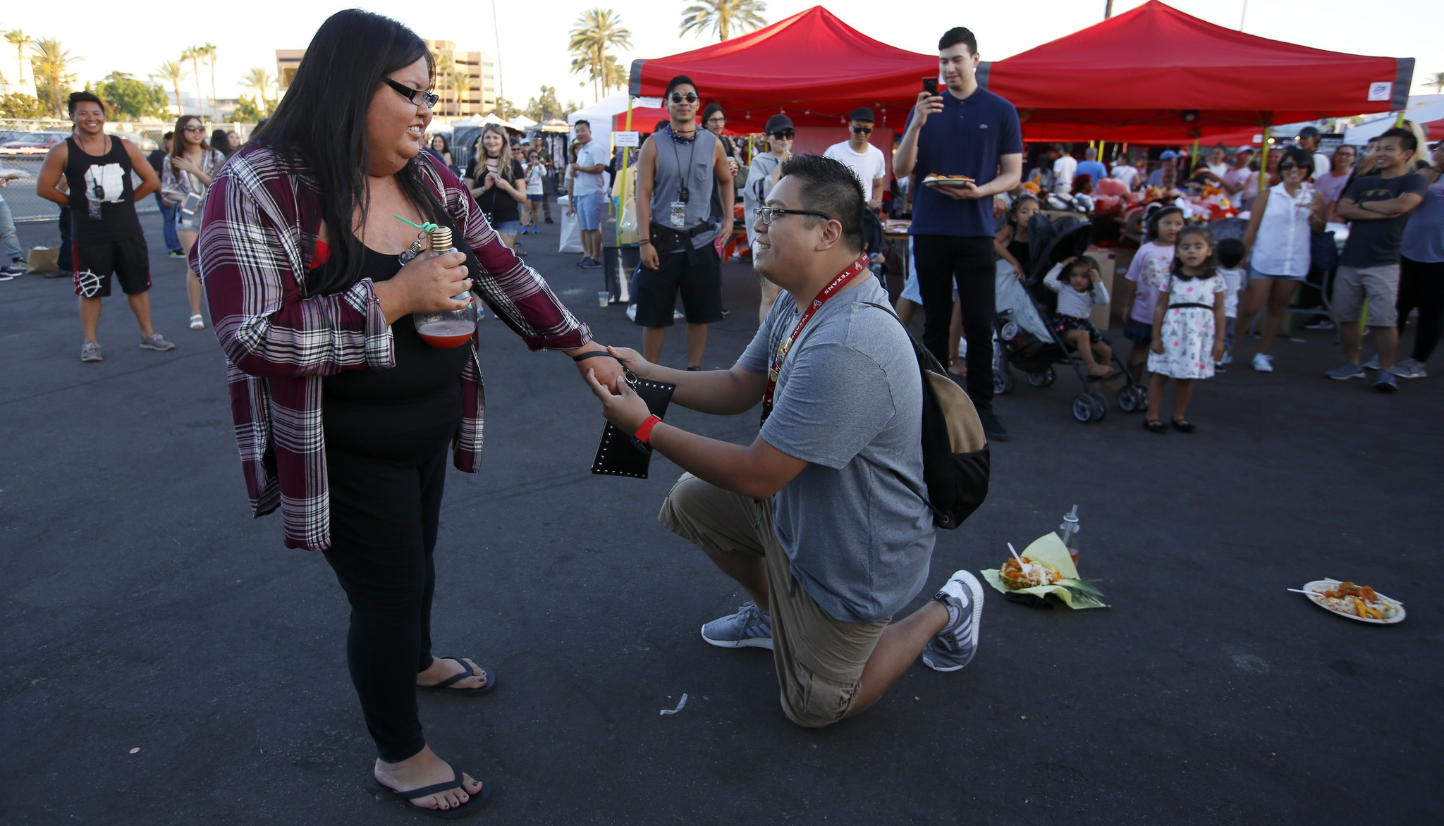 Lisa Thavisay listens while Steven Ham proposes at the 626 Night Market in Arcadia.