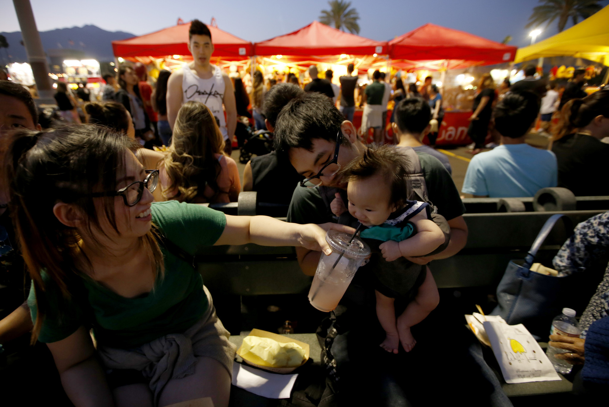 Linda Lee and Sam Man share a cold drink with their daughter, Olivia Man, 6 months, at a crowded 626 Night Market in Arcadia.