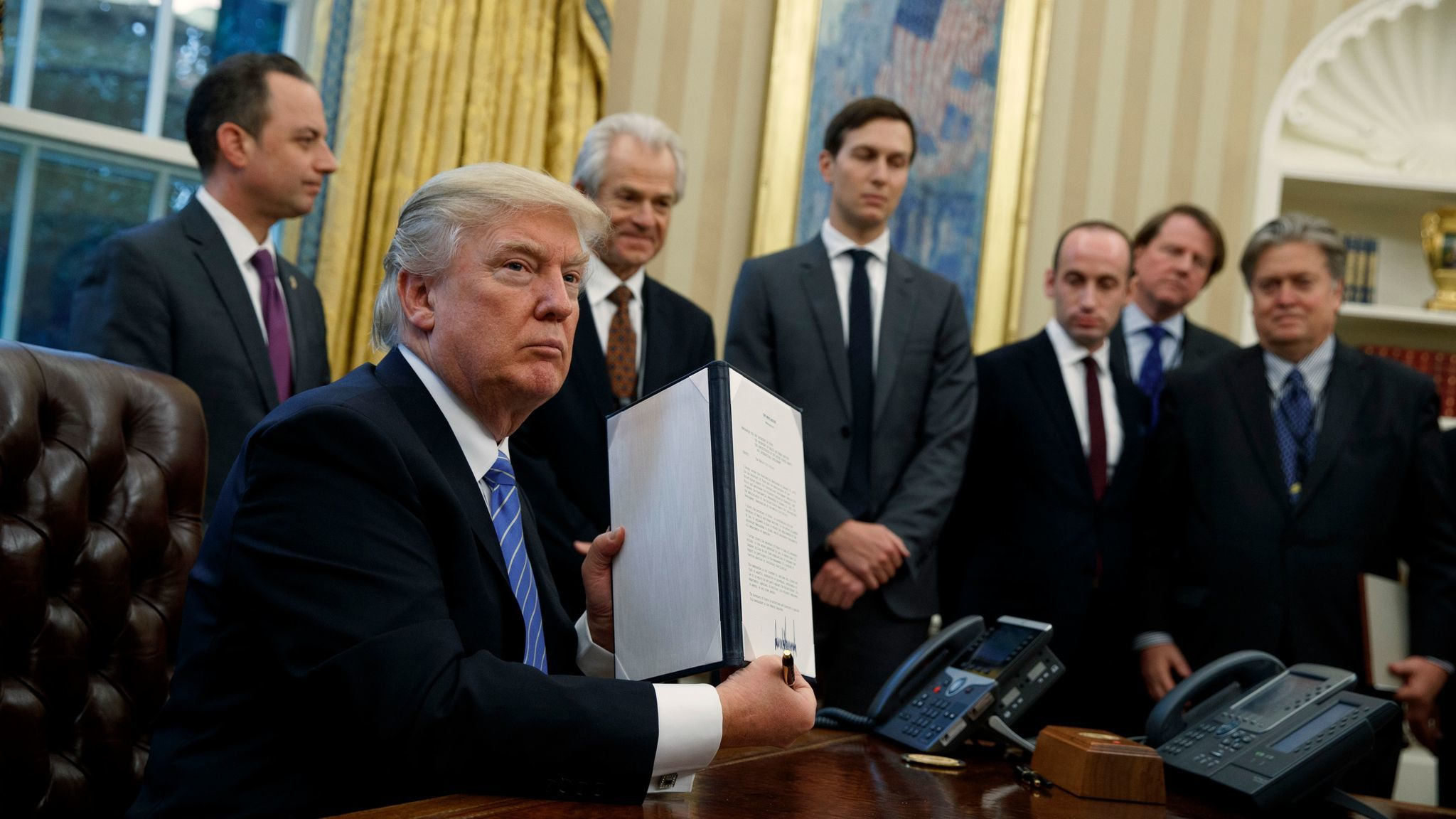 President Trump shows off a signed executive order reinstating a ban on funding for international organizations that provide abortion services or related counseling.