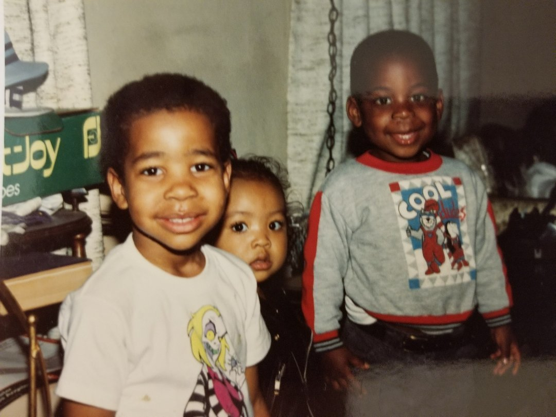 De'Von Hall smiles with his cousins in a photograph from around 1991.
